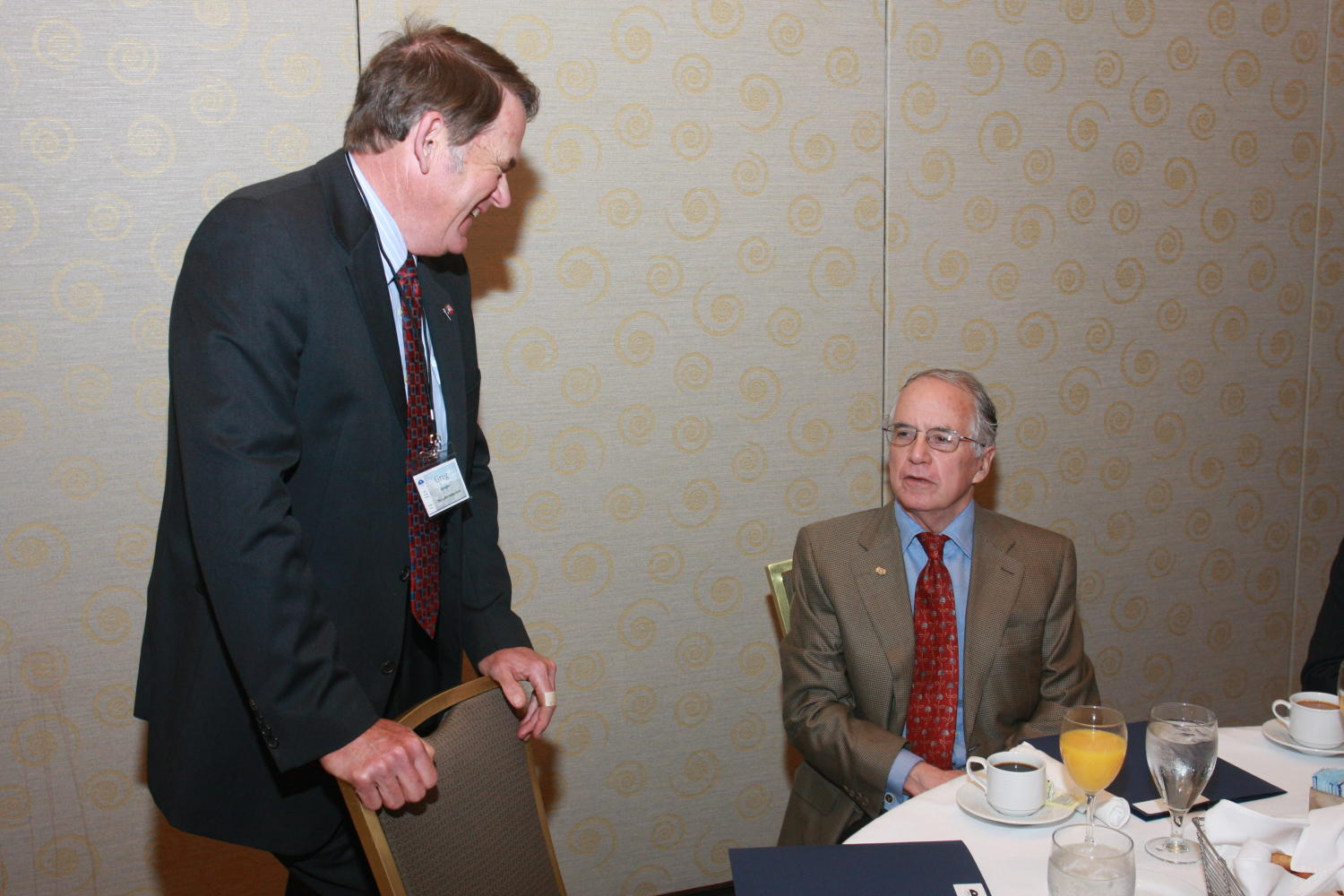 [Greg Shrader talking with other guest at TDNA conference], Photograph of Greg Shrader (left) talking with an unidentified guest seated at a table at the 2010 Texas Daily Newspaper Association annual meeting held in Houston, Texas.,
