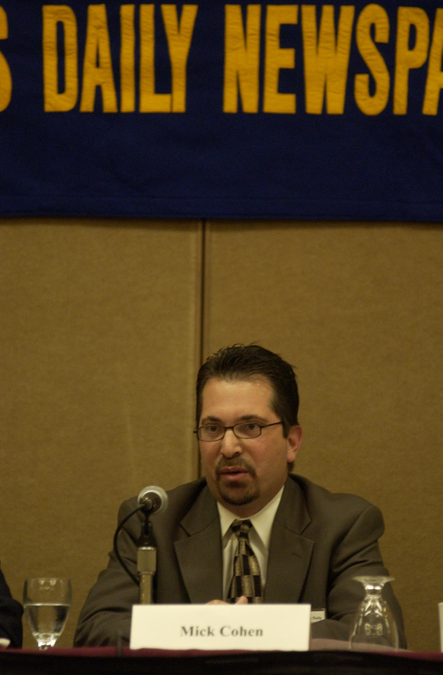 [Mick Cohen at the TDNA conference], Photograph of Mick Cohen in attendance at the 2004 Texas Daily News Association annual conference held in Corpus Christi. Cohen is seen sitting behind a table and sitting in front of a microphone as he is a guest speaker on a panel.,