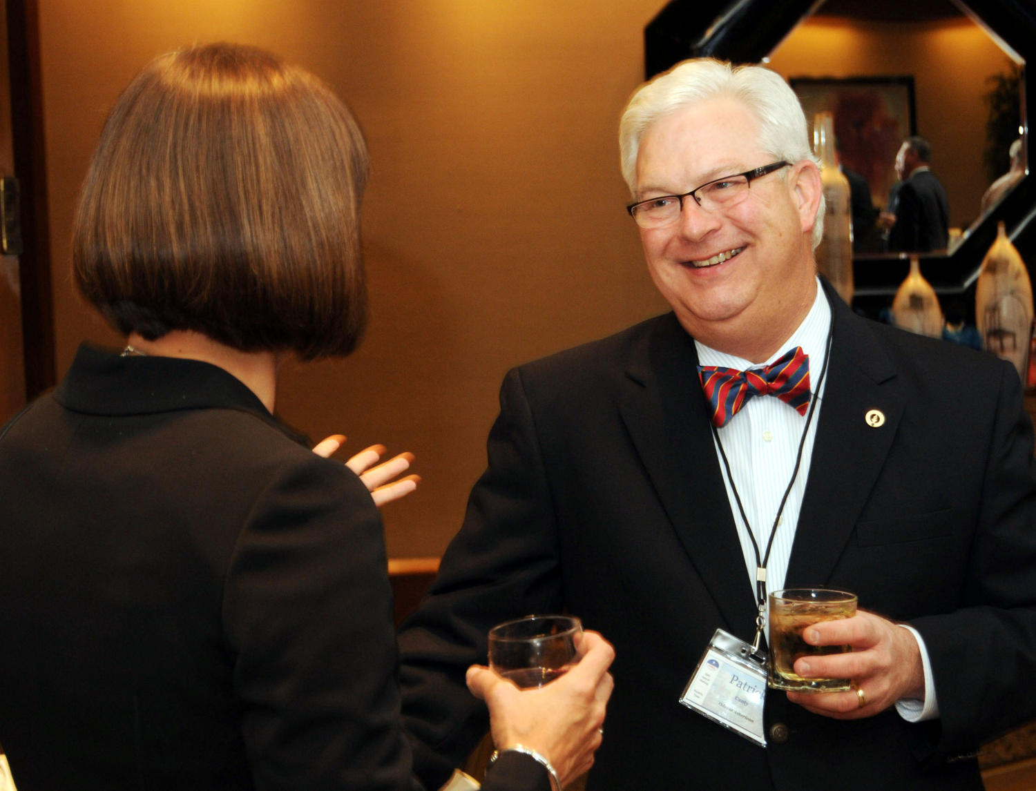 [Patrick Canty chatting at TDNA reception], Photograph of Patrick Canty (right) chatting with an unidentified woman and drinking refreshments during a reception at the 2010 Texas Daily Newspaper Association annual meeting held in Houston, Texas.,