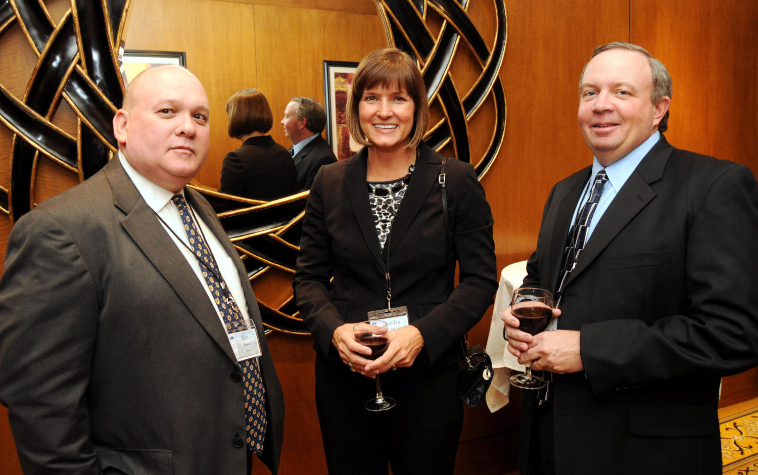 [Ken Whalen and Sandra Aven], Photograph of Ken Whalen (left), Sandra Aven (center) and an unidentified third man standing together in front of a large wall mirror and talking when their picture was taken during the 2010 Texas Daily Newspaper Association annual meeting held in Houston, Texas.,
