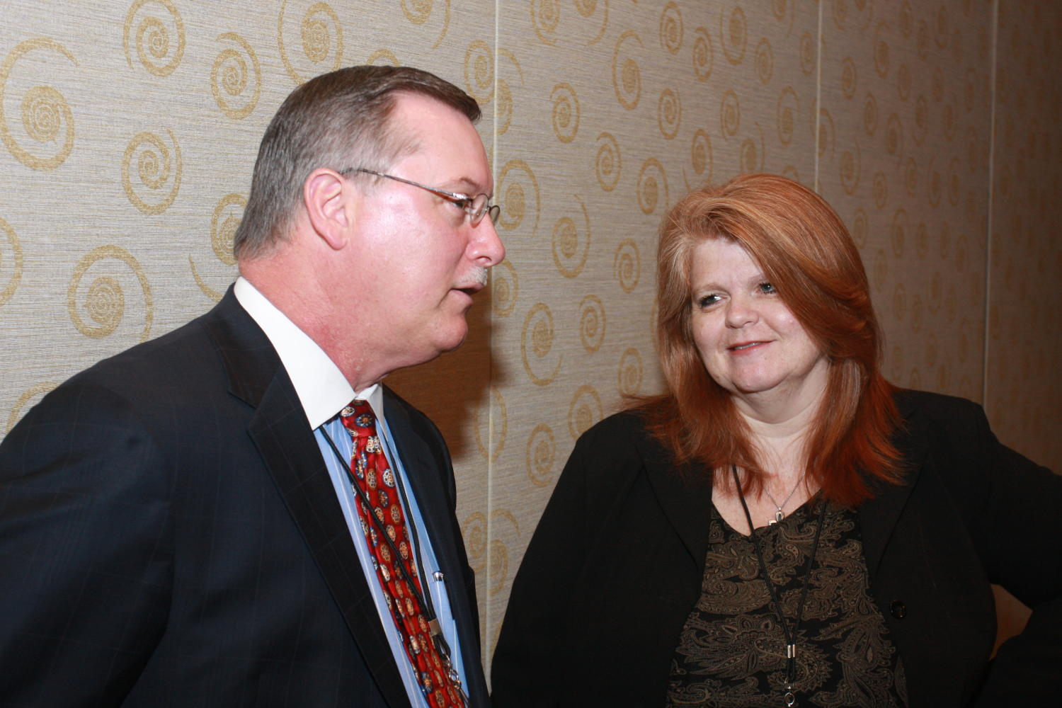 [Two guests attending TDNA conference], Photograph of two unidentified guests seen talking with one another during the 2010 Texas Daily Newspaper Association annual meeting held in Houston, Texas.,