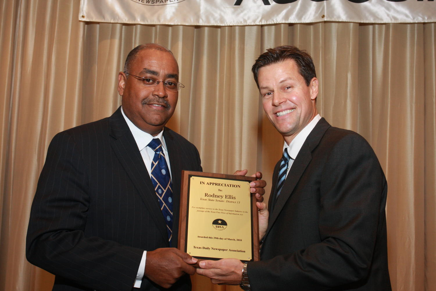"[Fred K. Hartman presenting Rodney Ellis with an award], Photograph of Fred K. Hartman (right) presenting Rodney Ellis (left) with an award during the 2010 Texas Daily Newspaper Association annual meeting held in Houston, Texas. The award reads, ""In Appreciation to: Rodney Ellis. Texas State Senate: District 13."","