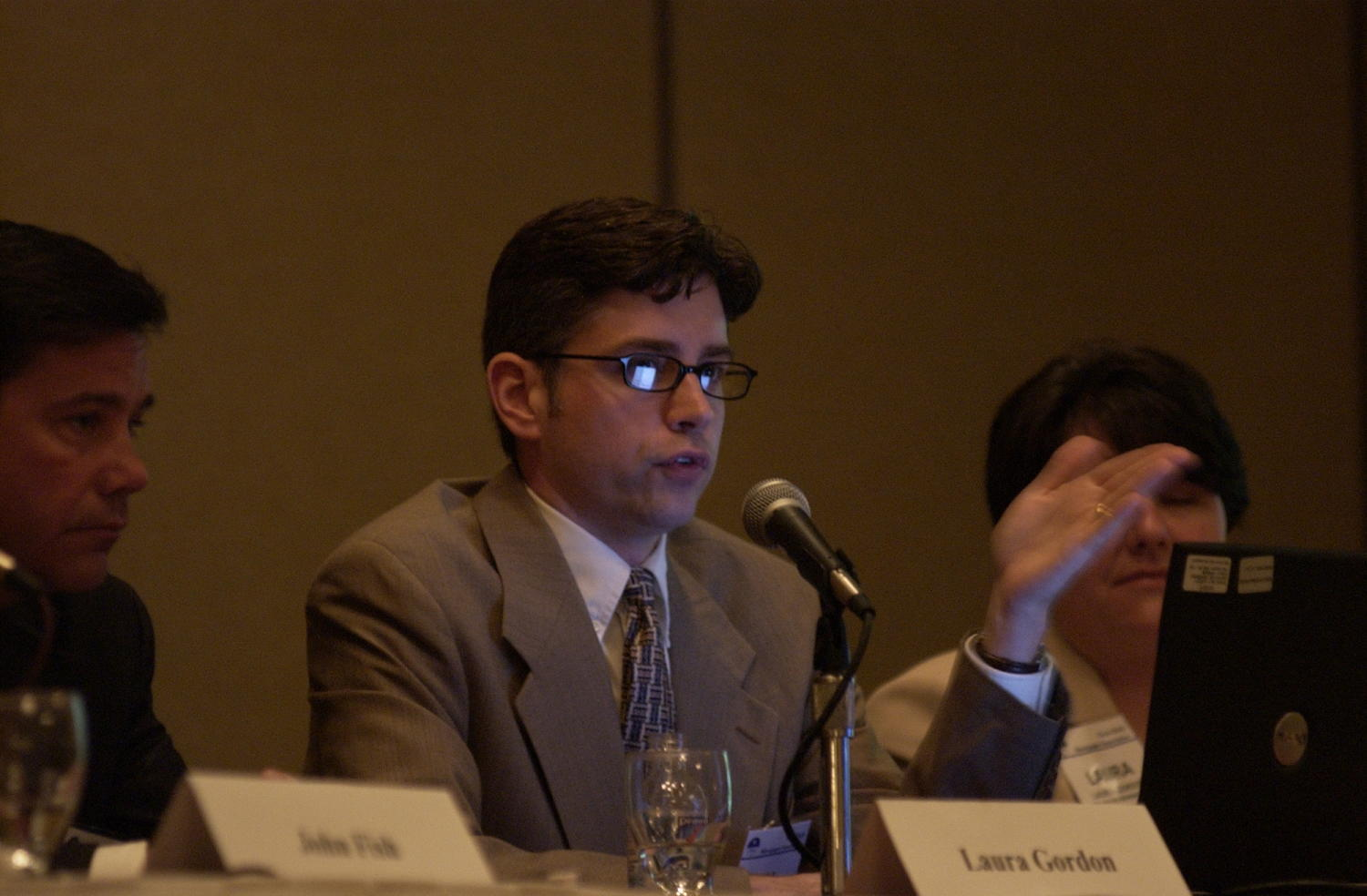 [Jim Lenahan giving a presentation at a TDNA conference, 2], Photograph of Jim Lenahan, a guest speaker attending the 2004 Texas Daily News Association annual conference held in Corpus Christi. Lenahan is seated behind a table and in front of a microphone addressing the audience of the conference as he gives a presentation.,