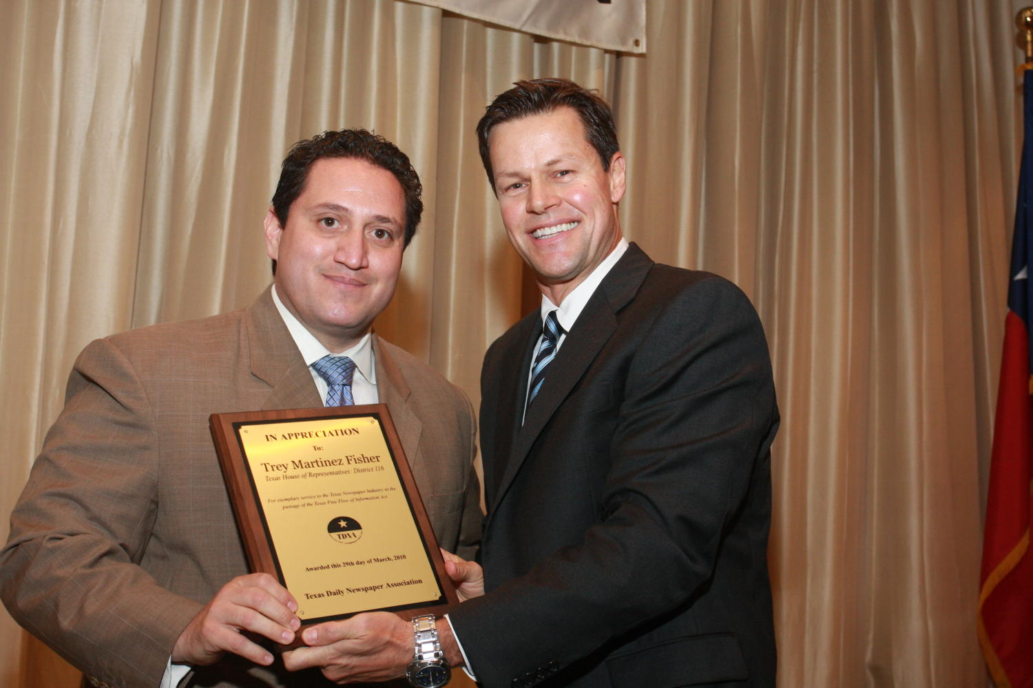 "[Fred K. Hartman presenting award to Trey Martinez Fisher], Photograph of Fred K. Hartman (right) presenting an award to Trey Martinez Fisher (left) during the 2010 Texas Daily Newspaper Association annual meeting held in Houston, Texas. The award reads, ""In Appreciation to: Trey Martinez Fisher, Texas House of Representatives: District 116."","