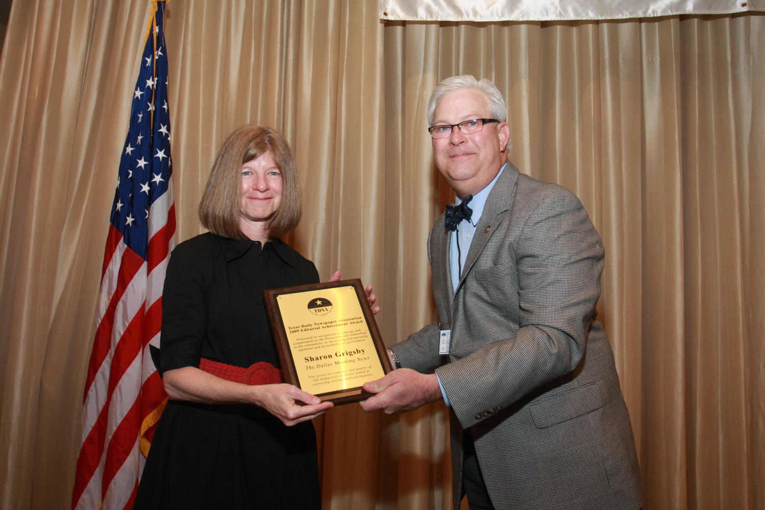"[Sharon Grigsby receiving award at TDNA conference], Photograph of Sharon Grigsby (left) receiving an award from Patrick Canty (right) during the 2010 Texas Daily Newspaper Association annual meeting held in Houston, Texas. The award reads, ""Texas Daily Newspaper Association 2009 Editorial Achievement Award. Presented in recognition of courage and commitment to the Newsroom and leadership in the community, in advocating and pursuing openness and accessibility to government. Sharon Grigsby, The Dallas Morning News. For series on economic and quality of life disparities in Dallas aimed at correcting institutionalized injustice."","
