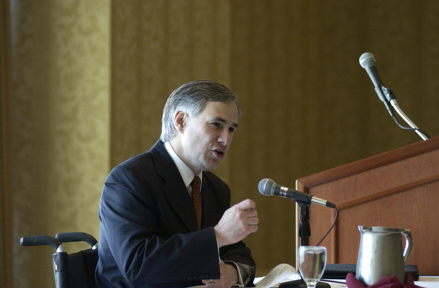 [Unidentified man attending the TDNA conference, 3], Photograph of an unidentified man seated in a chair and attending the 2004 Texas Daily News Association annual conference held in Corpus Christi. The man is seen speaking into the microphone placed in front of him and addressing the conference attendees.,
