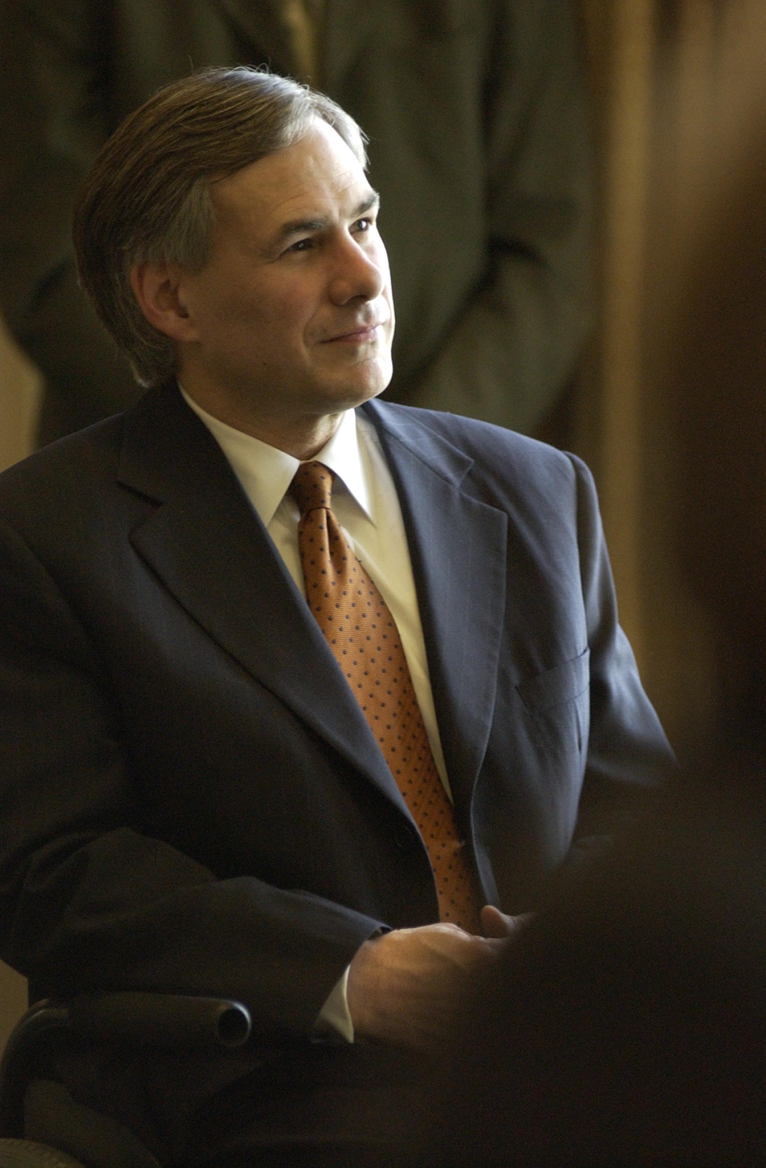 [Greg Abbott attending the TDNA conference], Photograph of Texas Attorney General Greg Abbott seated in a chair and attending the 2004 Texas Daily News Association annual conference held in Corpus Christi. Abbott is looking off to the right at something not visible in the photograph.,