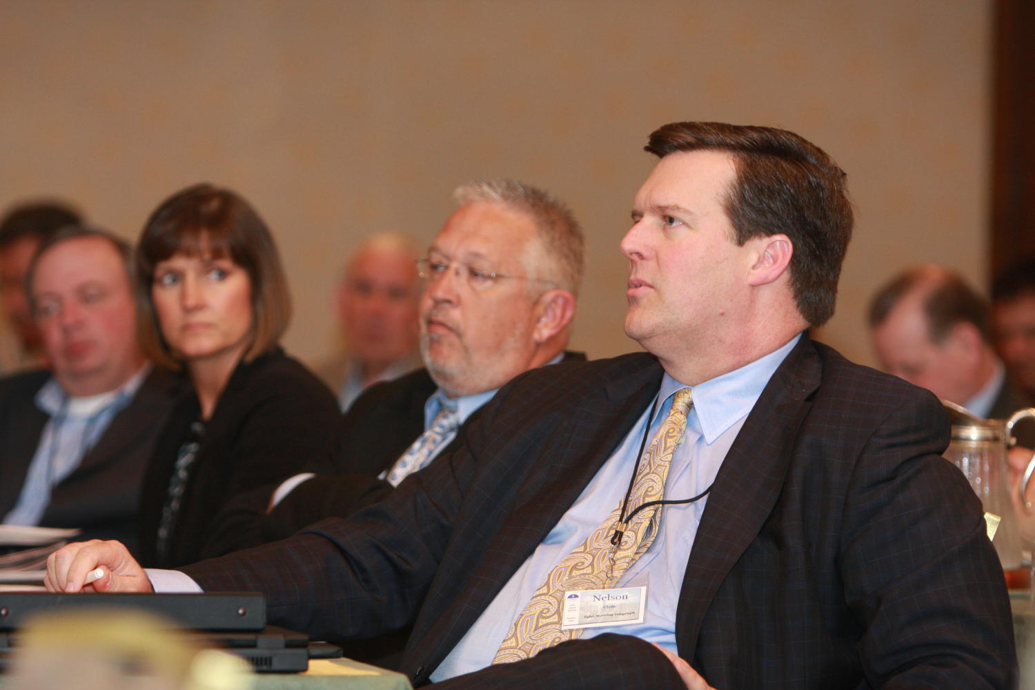 [Nelson Clyde IV seated and attending a TDNA conference], Photograph of Nelson Clyde IV seated at elongated tables with other guests as they are attending the 2010 Texas Daily Newspaper Association annual meeting held in Houston, Texas. Sandra Aven can be seen seated at the same table as Clyde.,