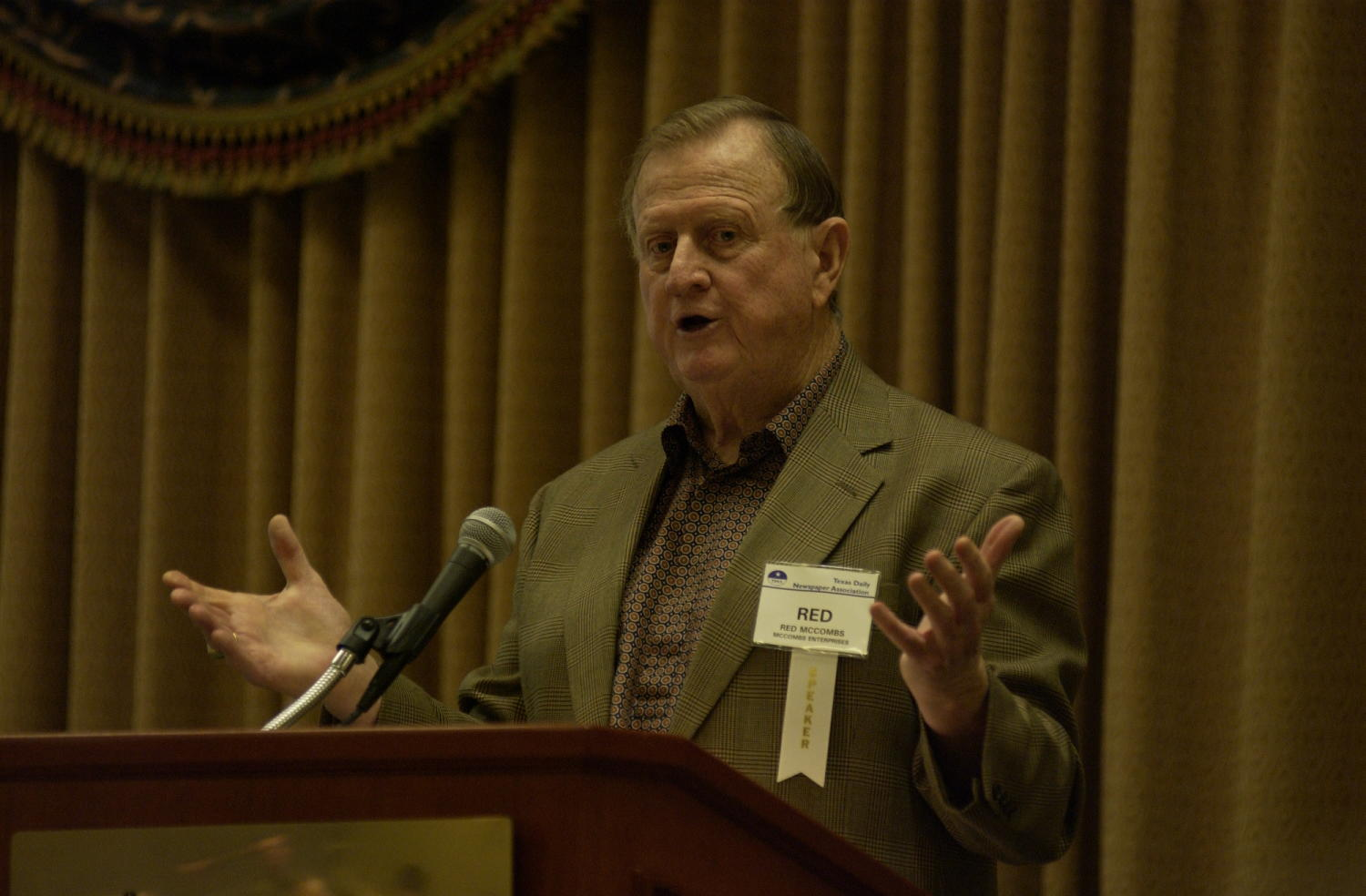 """[Billy Joe """"Red"""" McCombs guest speaking at TDNA conference, 3], Photograph of Billy Joe """"Red"""" McCombs of McCombs Enterprises, guest speaking at the 2004 Texas Daily News Association (TDNA) annual conference held in Corpus Christi. McCombs is seen standing at a podium and speaking into the microphone as he addresses the guests of the conference.,"""