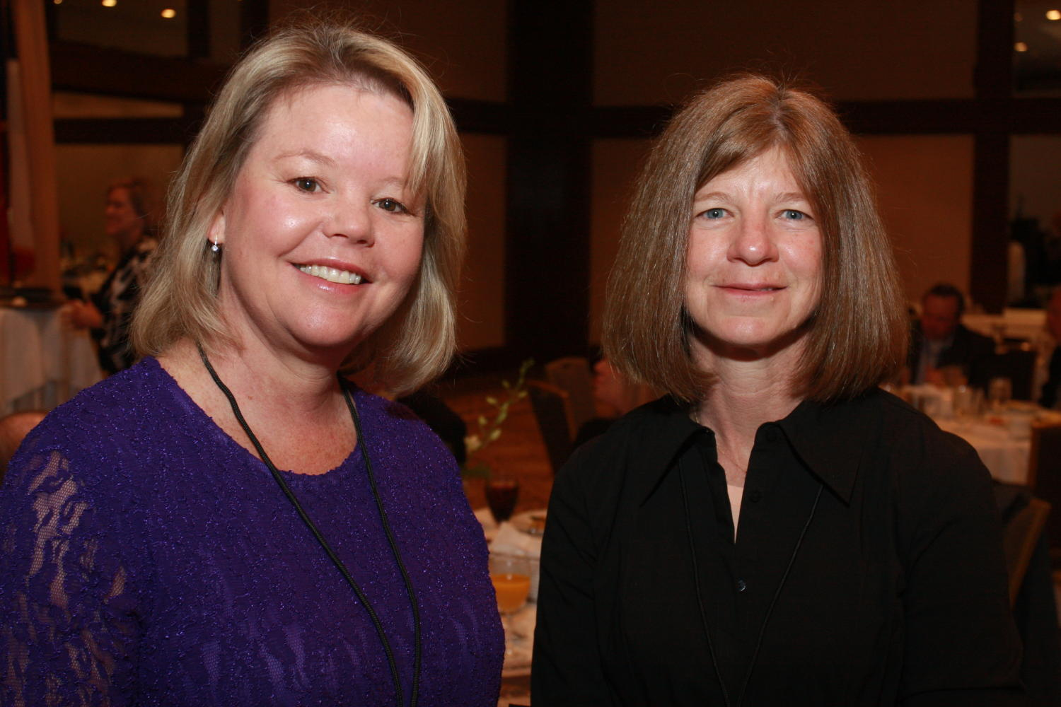 [Two women posing together at TDNA conference], Photograph of two women, one identified as Sharon Grigsby (right) standing together and smiling as their picture is taken during the 2010 Texas Daily Newspaper Association annual meeting held in Houston, Texas.,