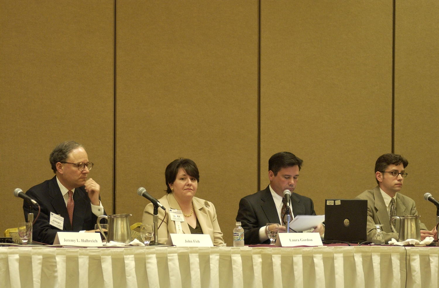 [Jeremy L. Halbreich, Laura Gordon, John Fish and Jim Lenahan], Photograph of (L-R) Jeremy L. Halbreich, Laura Gordon, John Fish and Jim Lenahan, guest speakers attending the 2004 Texas Daily News Association annual conference held in Corpus Christi. Fish is seen sitting in front of a laptop and reading from his notes as he gives a presentation to the conference goers, his fellow guest speakers sit on either side of him and listen.,
