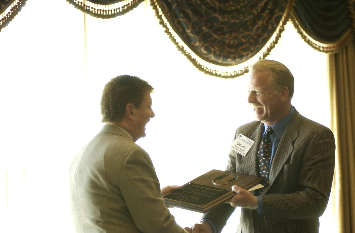 [Donnis Baggett handing out a John Murphy Award], Photograph of Donnis Baggett (right) handing out a man identified as Vic the John Murphy Award the 2004 Texas Daily News Association annual conference held in Corpus Christi. Baggett and the man are shaking hands as Baggett gives him the engraved plaque.,