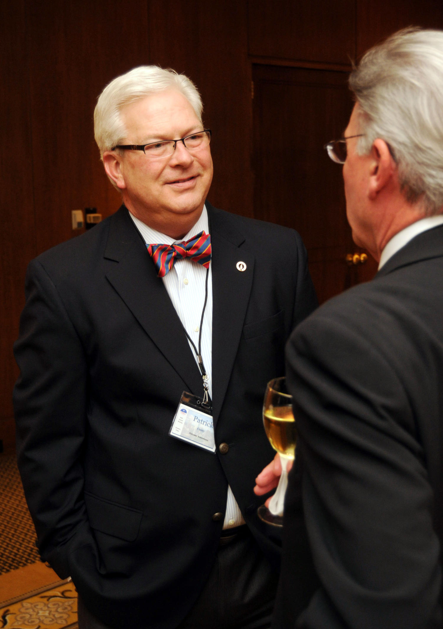 [Patrick Canty talking with conference attendee], Photograph of Patrick Canty talking with an unidentified man, as they are in a hall with other guests who are attending the 2010 Texas Daily Newspaper Association annual meeting held in Houston, Texas.,