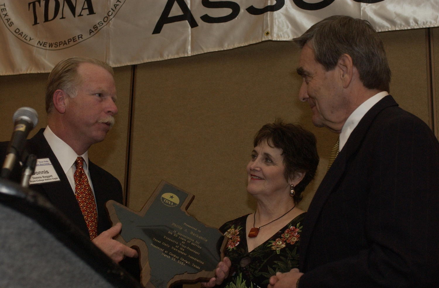 [Donnis Baggett presenting an award to Phillip A. Berkebile, 2], Photograph of Donnis Baggett (left) presenting an award to Phillip A. Berkebile and a woman presumed to be his wife, during the 2004 Texas Daily News Association annual conference held in Corpus Christi.,
