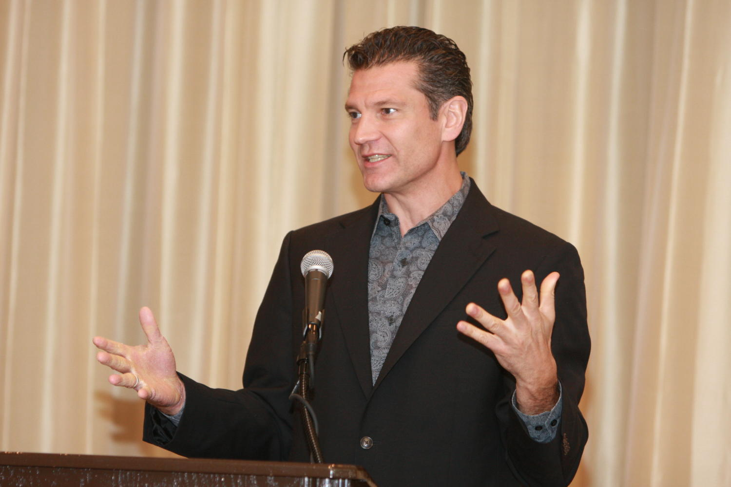 [Unidentified man giving a speech at the TDNA conference], Photograph of an unidentified man standing at a podium and speaking into a microphone as he gives a speech during the 2010 Texas Daily Newspaper Association annual meeting held in Houston, Texas.,