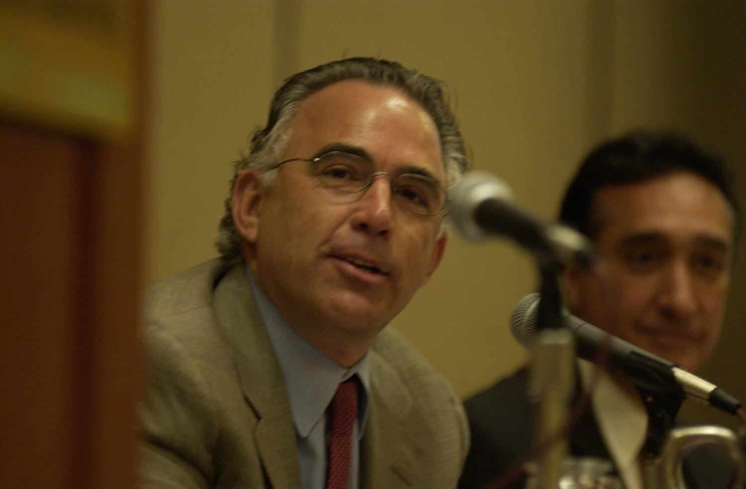 [Unidentified guest at TDNA conference], Photograph of an unidentified guest speaker attending the 2004 Texas Daily News Association annual conference held in Corpus Christi. The guest is seated at the table with other speakers with microphones placed in front of them.,