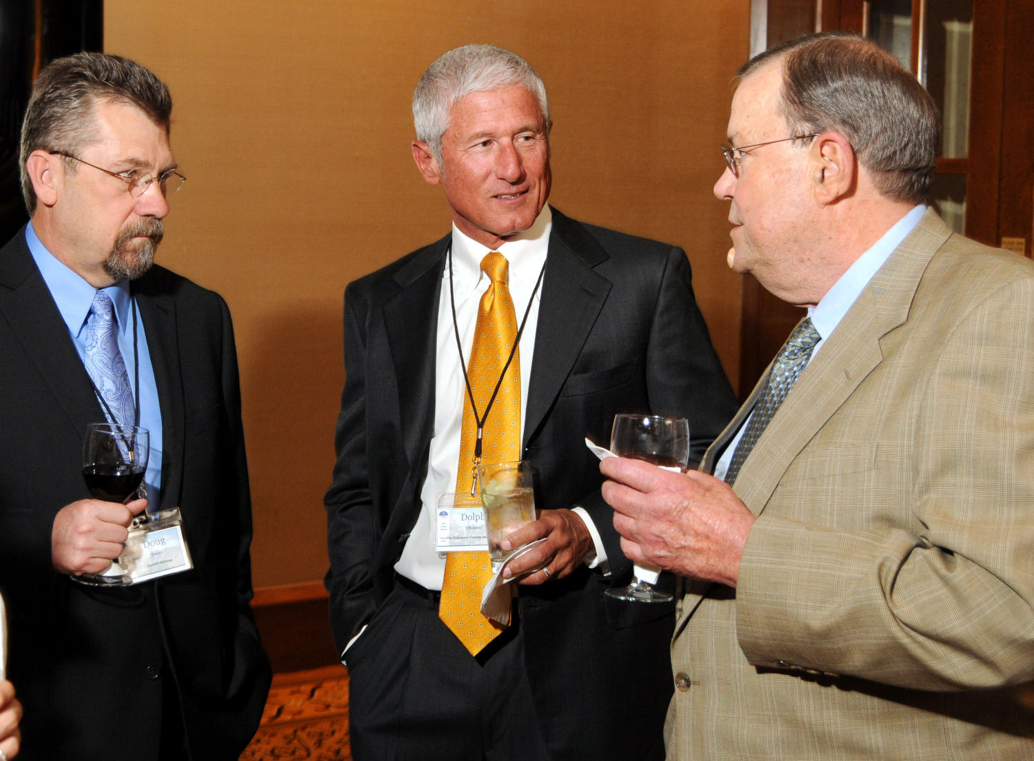 [Doug Toney and Dolph Tillotson], Photograph of Doug Toney (left), Dolph Tillotson (center) and an unidentified guest seen standing with one another chatting and drinking refreshments during a reception at the 2010 Texas Daily Newspaper Association annual meeting held in Houston, Texas.,