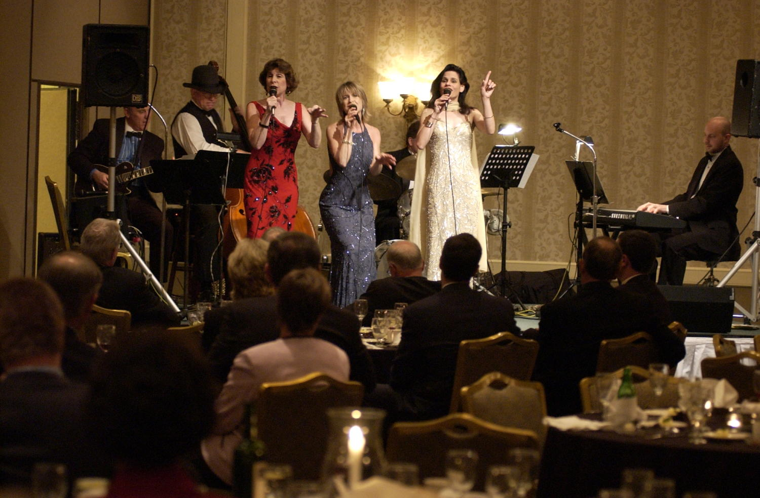 [Photograph of the entertainment at the TDNA conference], Photograph of female entertainers and their band performing at the 2004 Texas Daily News Association annual conference held in Corpus Christi. Conference goers are seen seated at their tables and looking up at the stage and the women perform their song for their crowd.,