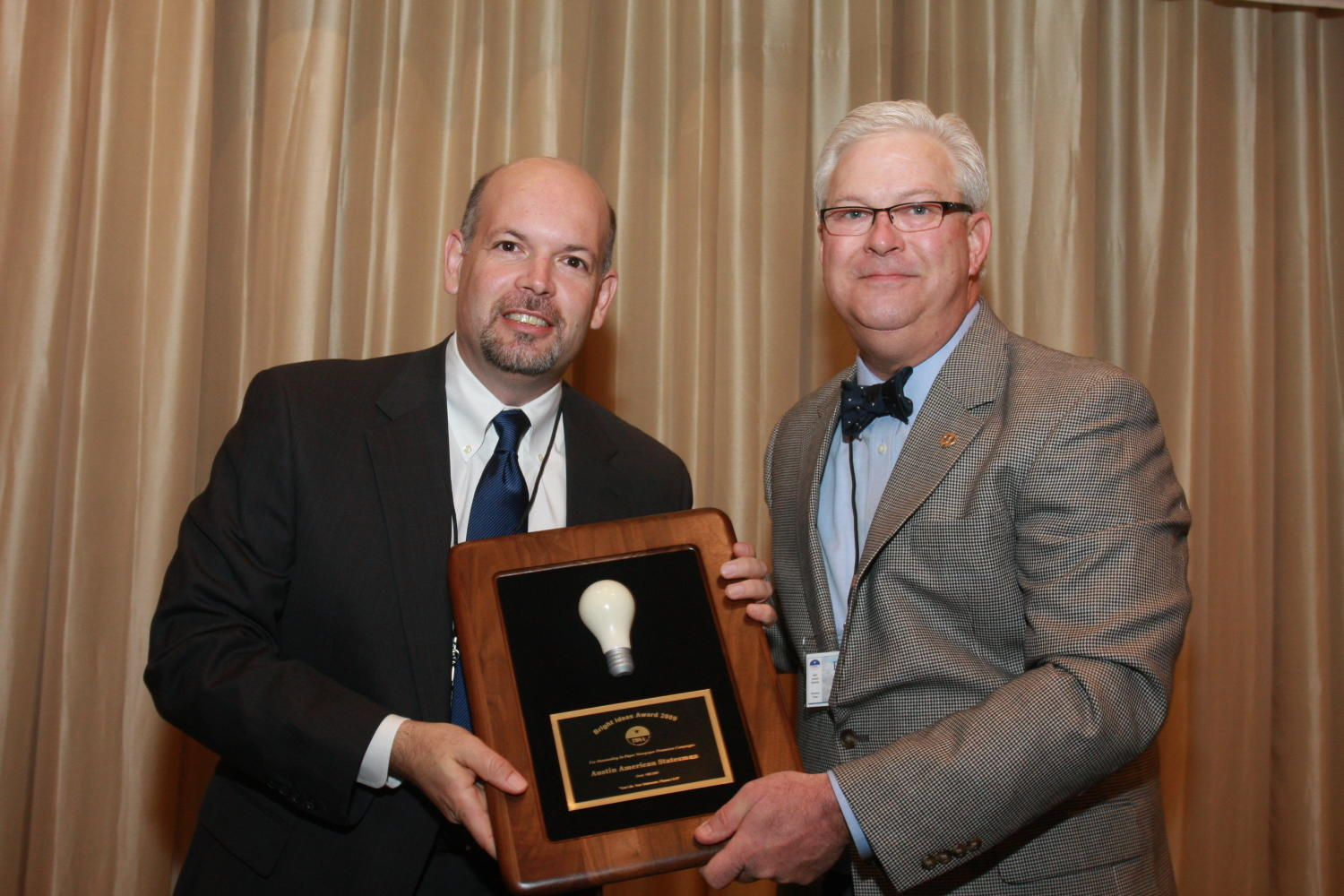 "[Man receiving award at TDNA conference], Photograph of an unidentified man (left) receiving an award from Patrick Canty (right) during the 2010 Texas Daily Newspaper Association annual meeting held in Houston, Texas. The award reads, ""Bright Idea Award 2009. Austin American-Statesman."","
