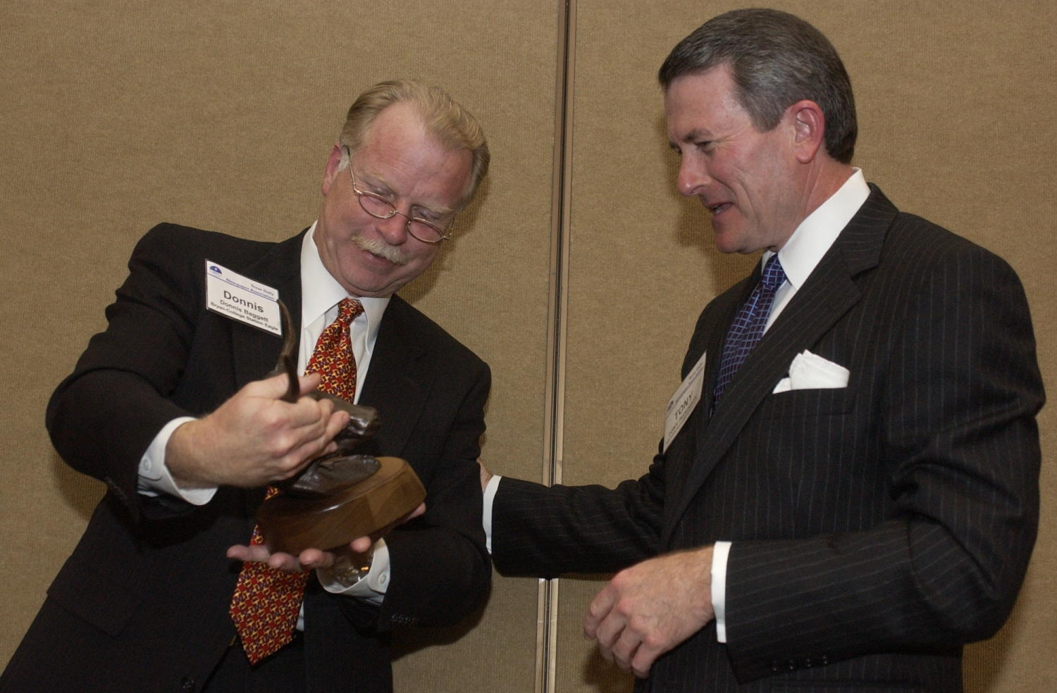 [Tony Pederson and Donnis Baggett], Photograph of Tony Pederson, of the Southern Methodist University and Donnis Baggett looking over an award together during the 2004 Texas Daily News Association annual conference held in Corpus Christi.,