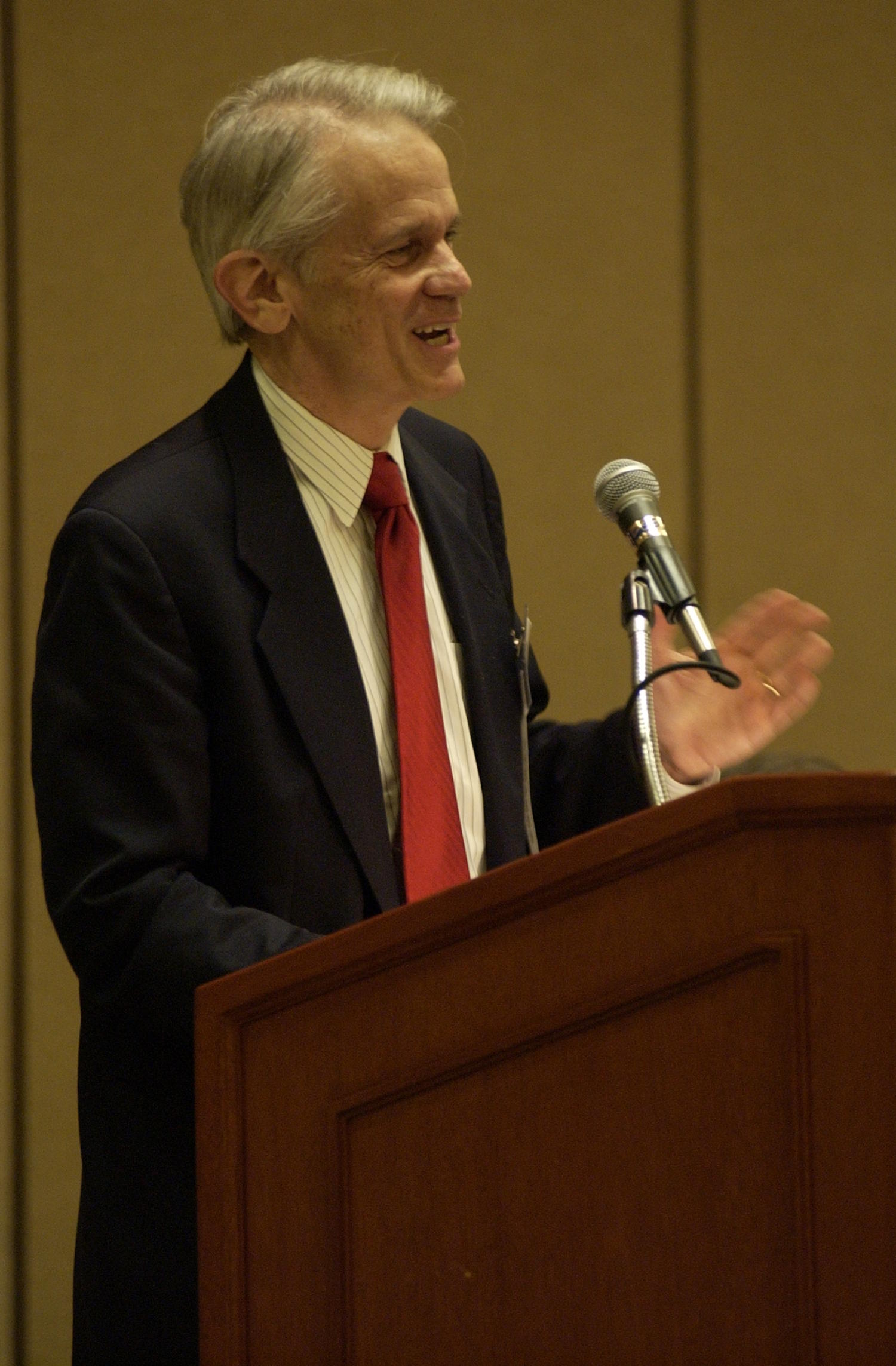 [Unidentified speaker at TDNA conference], Photograph of an unidentified guest speaker attending the 2004 Texas Daily News Association annual conference held in Corpus Christi. The guest is standing at a podium in the conference hall and talking into the microphone addressing the attendees.,