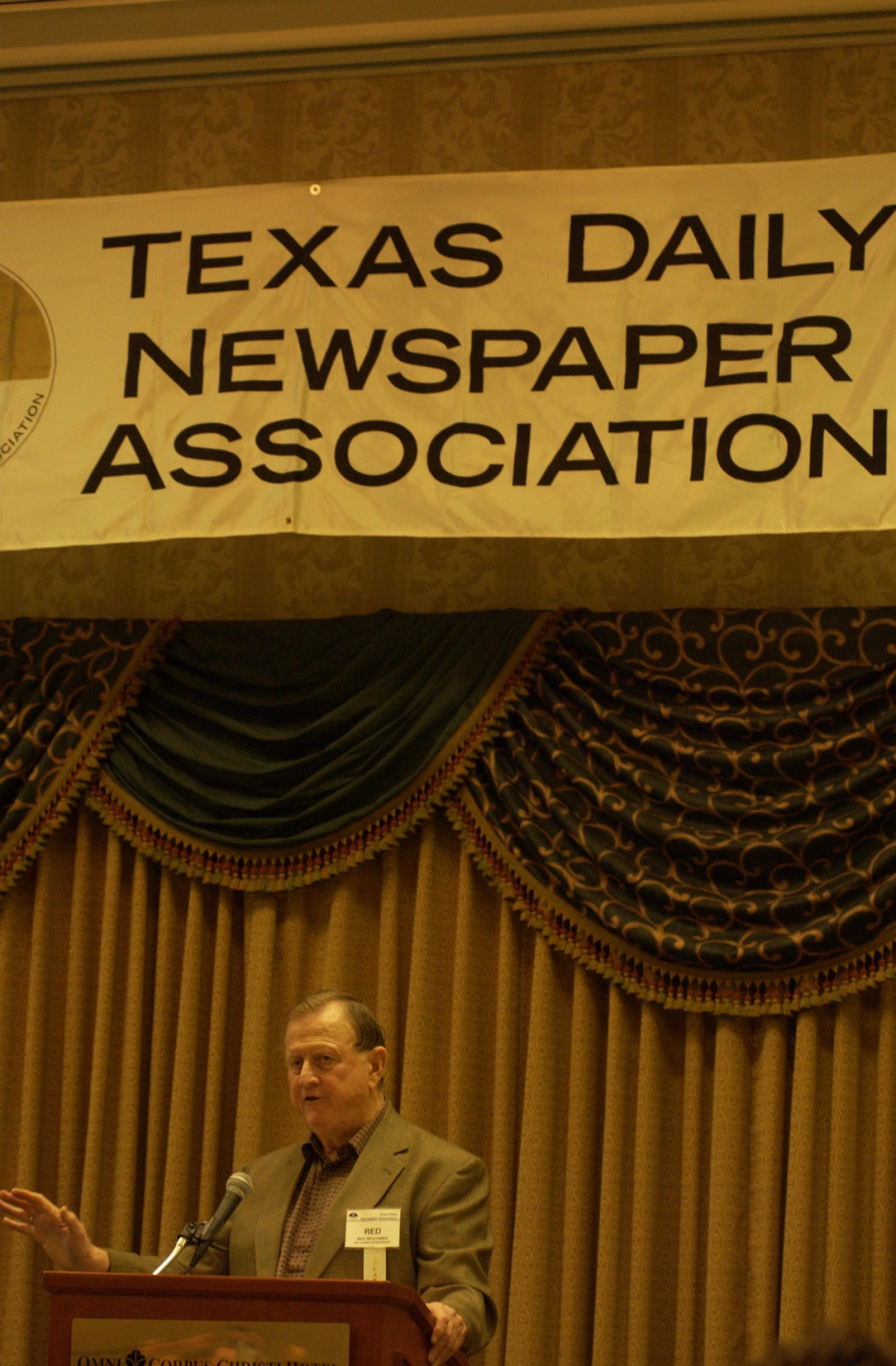 """[Billy Joe """"Red"""" McCombs guest speaking at TDNA conference], Photograph of Billy Joe """"Red"""" McCombs of McCombs Enterprises, guest speaking at the 2004 Texas Daily News Association (TDNA) annual conference held in Corpus Christi. McCombs is seen standing at a podium and speaking into the microphone as he addresses the guests of the conference.,"""