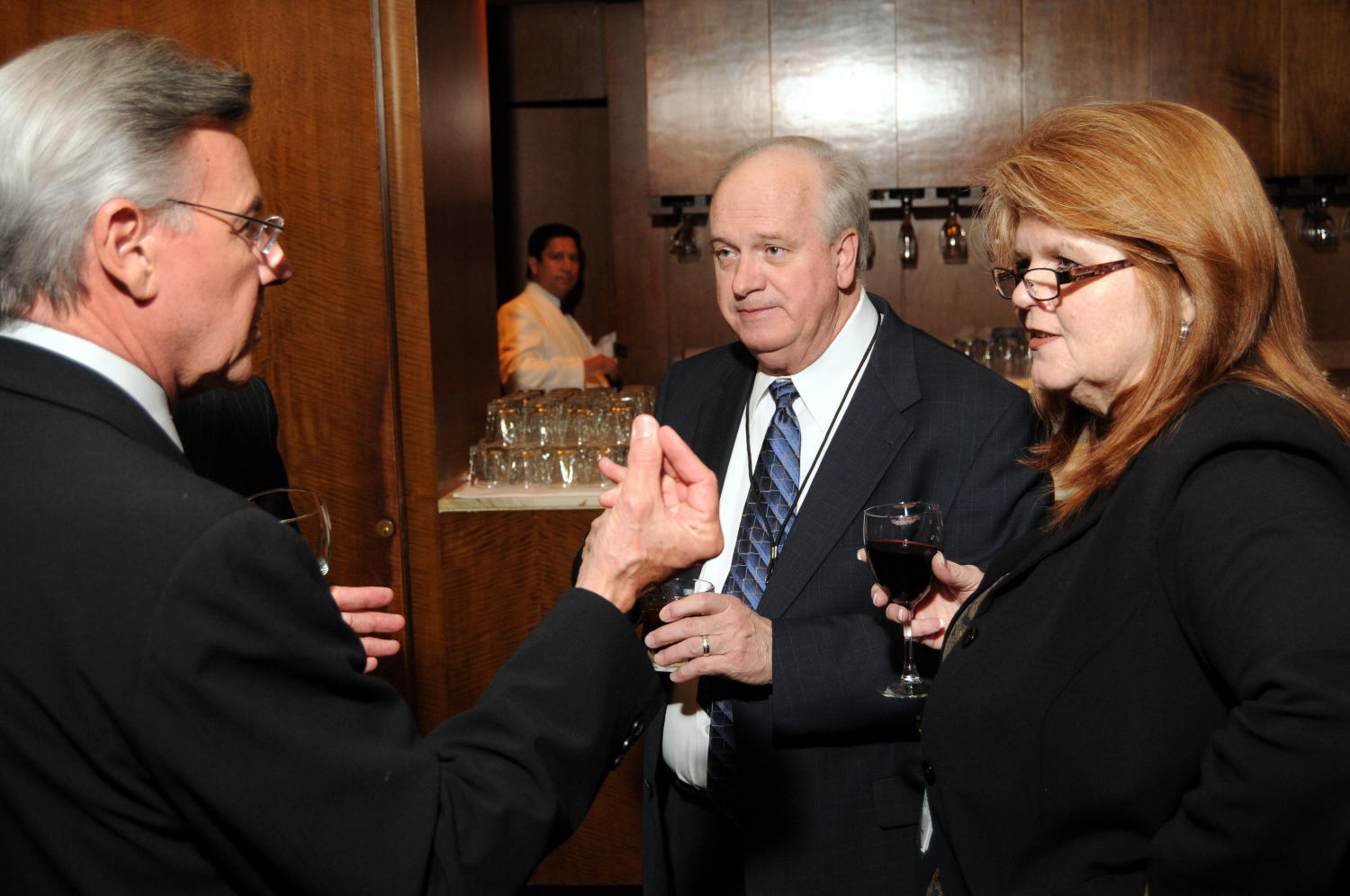 [Guests drinking refreshments at TDNA reception], Photograph of three unidentified guests conversing with one another and drinking refreshments during a reception at the 2010 Texas Daily Newspaper Association annual meeting held in Houston, Texas.,