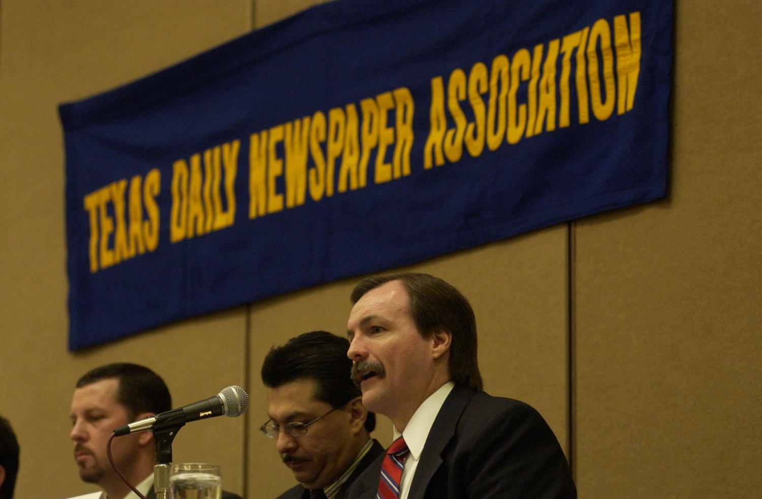 [Gene Haddock, Lorenzo Vigliante and Lane Aten], Photograph of (L-R) Gene Haddock, Lorenzo Vigliante and Lane Aten in attendance at the 2004 Texas Daily News Association annual conference held in Corpus Christi. All three men are seen seated behind a table and in front of a microphones as they are guest speakers at the conference.,
