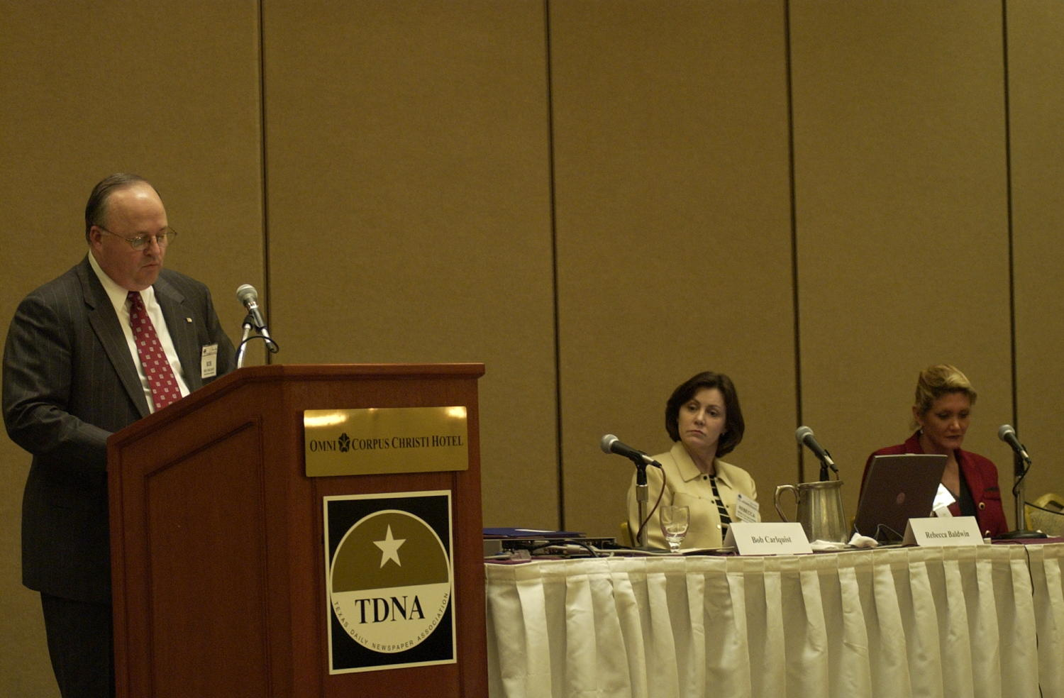 """[Bob Carlquist speaking at the TDNA conference in Corpus Christi, 2], Photograph of Bob Carlquist speaking to the conference attendees during the 2004 Texas Daily News Association annual conference held in Corpus Christi. Carlquist is seen standing behind the podium that reads, """"Omni Corpus Christi Hotel"""" and displays the TDNA emblem. Two women are seen sitting at the table to the right of the podium, the woman in yellow identified as Rebecca Baldwin by her name plate.,"""