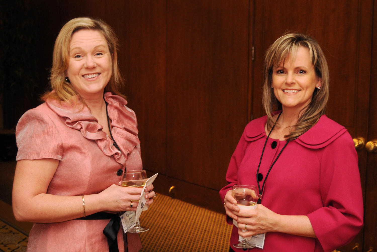 [Two women dressed in pink attending TDNA conference], Photograph of Cyndi Brown (left) and an unidentified woman attending the the 2010 Texas Daily Newspaper Association annual meeting held in Houston, Texas. Both women are dressed in shades of pink and holding refreshments in their hands.,