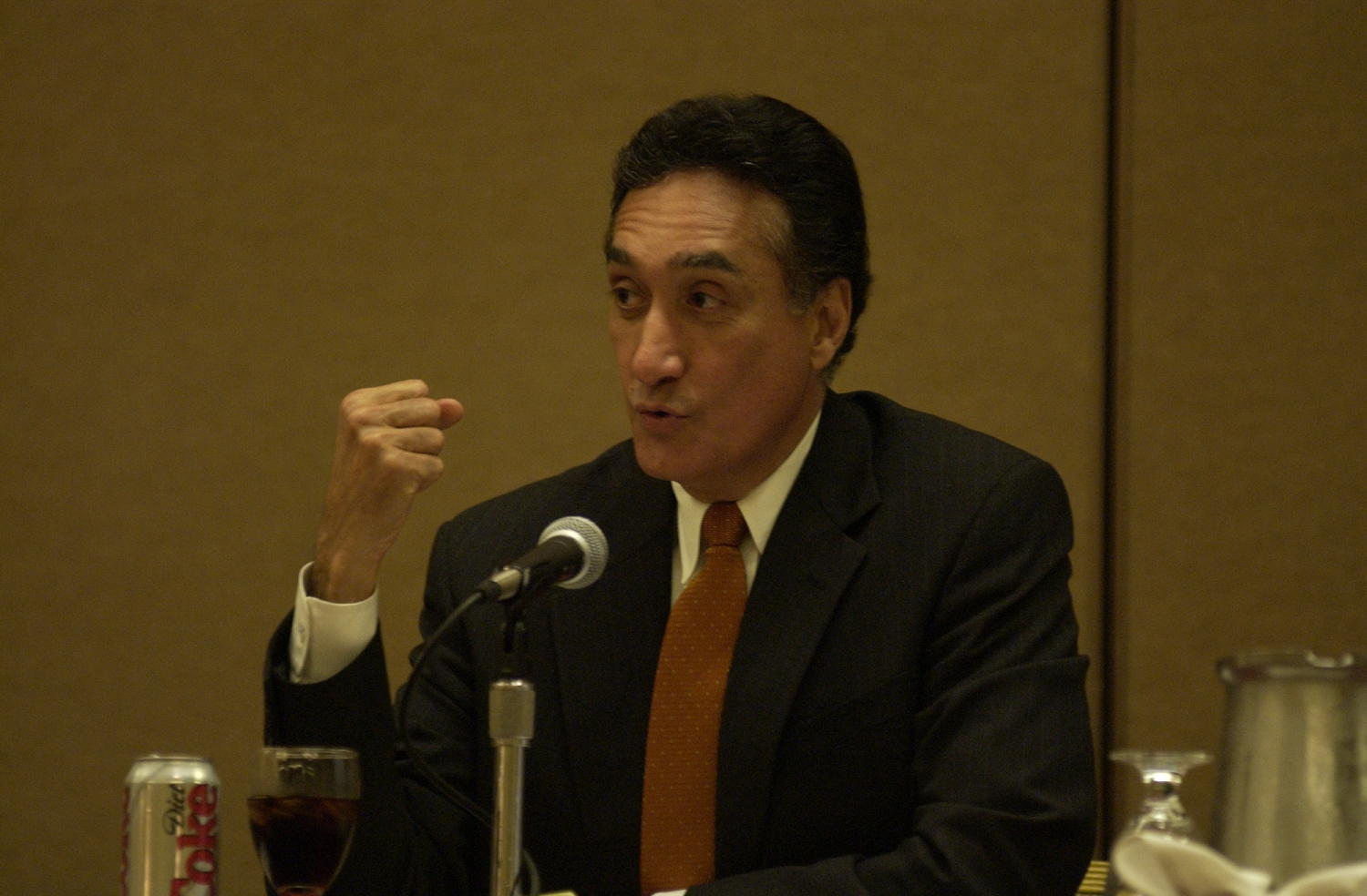 [Guest speaker at TDNA conference], Photograph of an unidentified guest speaker attending the 2004 Texas Daily News Association annual conference held in Corpus Christi. The guest is seated at a table and talking into a microphone addressing the conference attendees. A diet coke is opened and poured into a glass in front of him.,