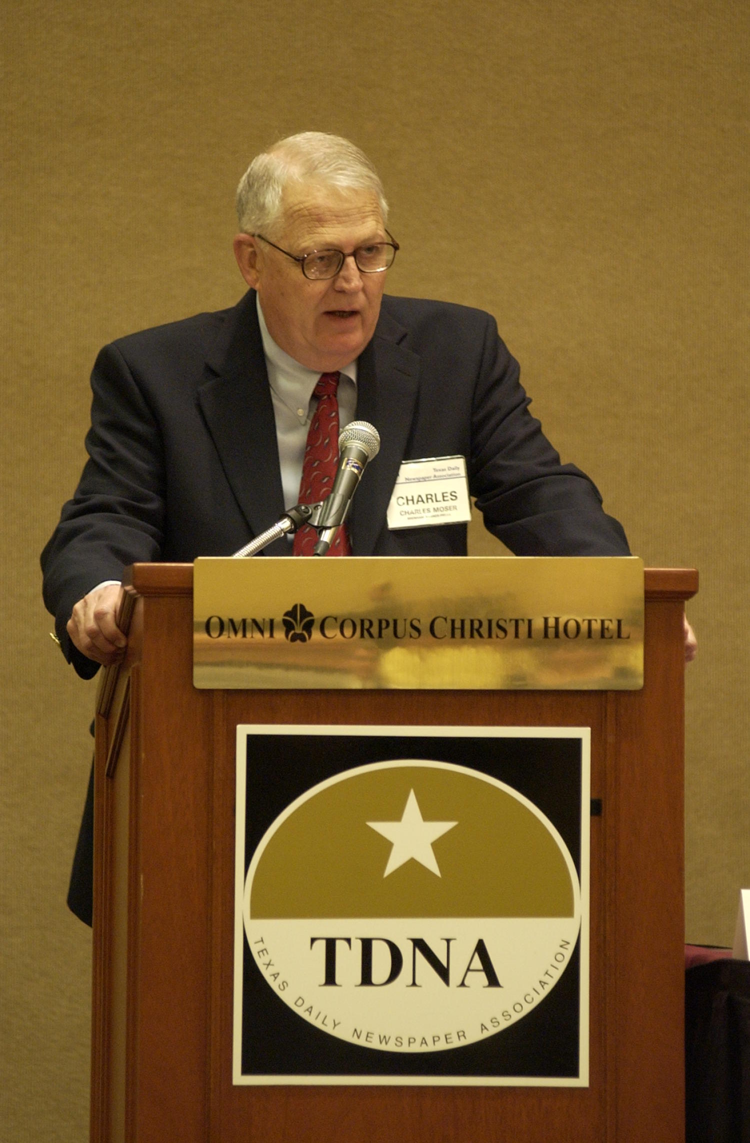 [Charles Moser speaking into microphone at TDNA conference], Photograph of Charles Moser speaking into a microphone during the 2004 Texas Daily News Association annual conference held in Corpus Christi.,