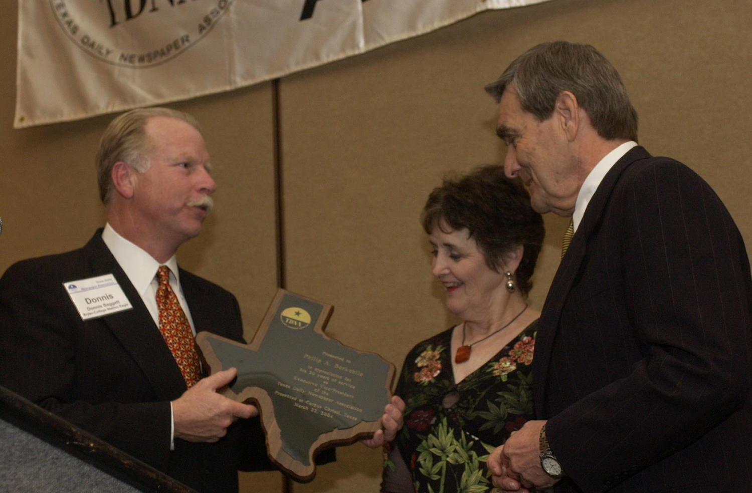 [Donnis Baggett presenting an award to Phillip A. Berkebile], Photograph of Donnis Baggett (left) presenting an award to Phillip A. Berkebile and a woman presumed to be his wife, during the 2004 Texas Daily News Association annual conference held in Corpus Christi.,