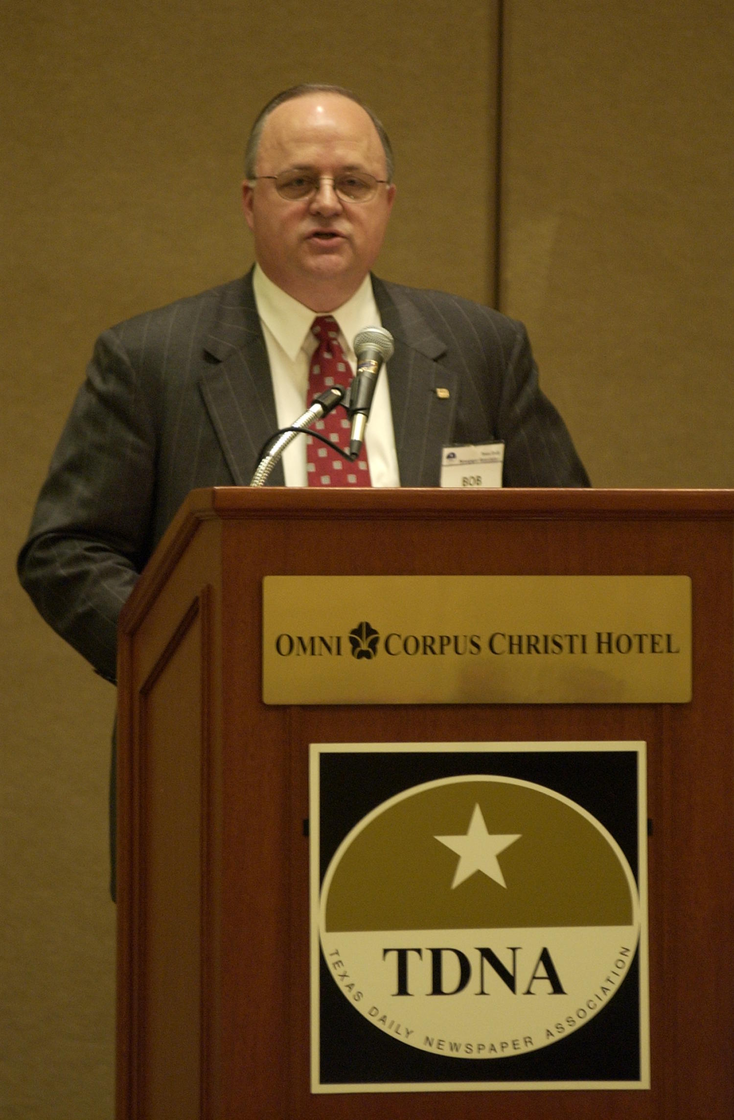 """[Bob Carlquist speaking at the TDNA conference in Corpus Christi], Photograph of Bob Carlquist speaking to the conference attendees during the 2004 Texas Daily News Association annual conference held in Corpus Christi. Carlquist is seen standing behind the podium that reads, """"Omni Corpus Christi Hotel"""" and displays the TDNA emblem.,"""