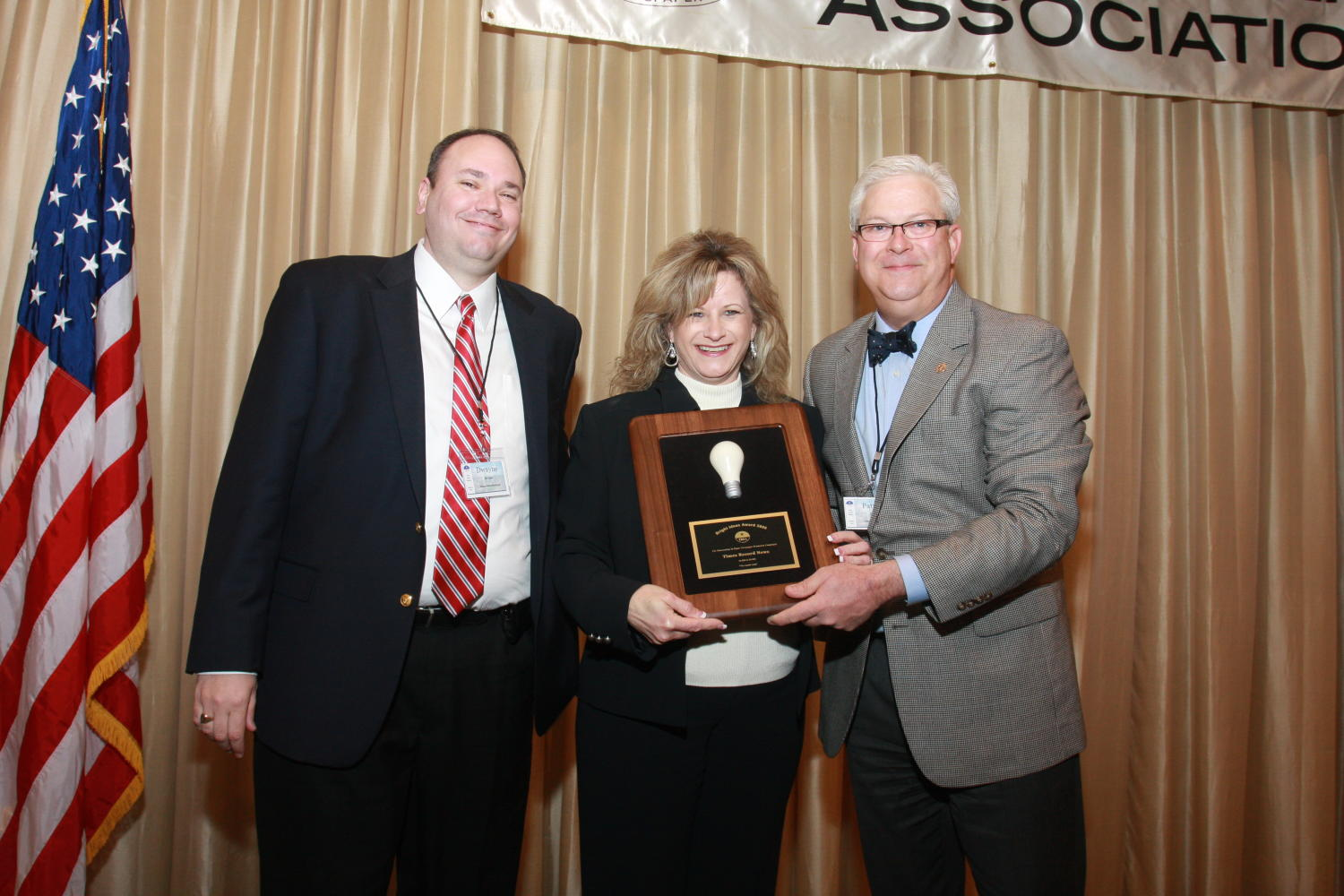 "[Woman receiving award at TDNA conference], Photograph of an unidentified woman (center) receiving an award from Patrick Canty (right) during the 2010 Texas Daily Newspaper Association annual meeting held in Houston, Texas. The award reads, ""Bright Idea Award 2009. Times Record News."" The man on the left has been identified as Dwayne.,"