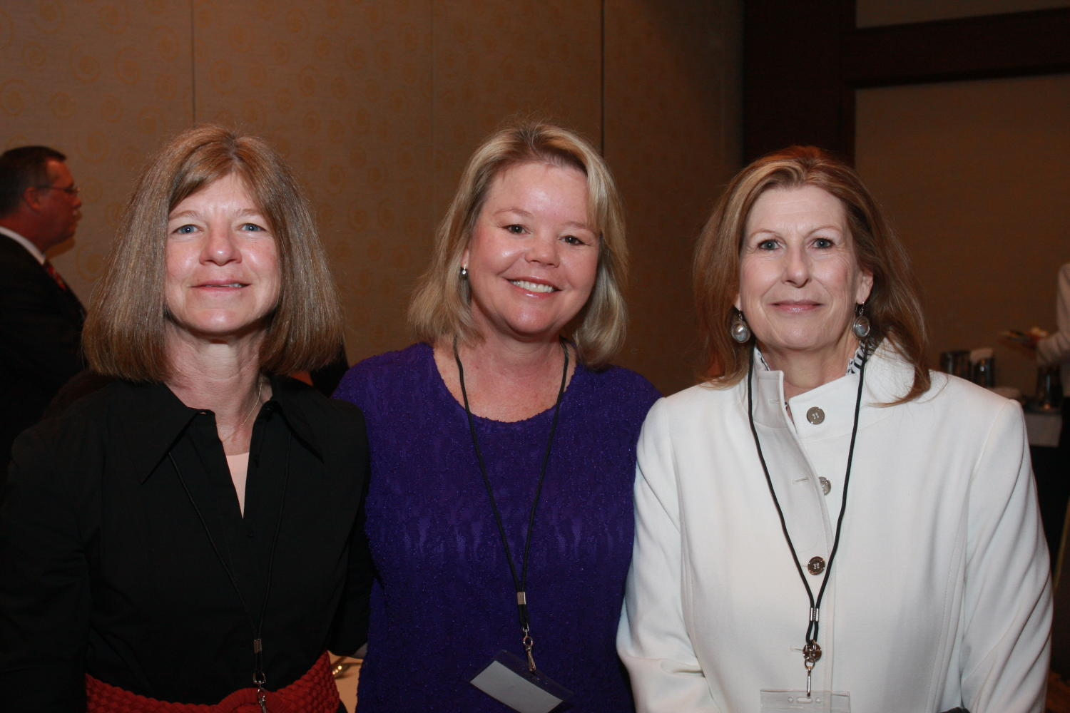[Three women posing together at TDNA conference], Photograph of three women, one identified as Sharon Grigsby (left) standing together and smiling as their picture is taken during the 2010 Texas Daily Newspaper Association annual meeting held in Houston, Texas.,