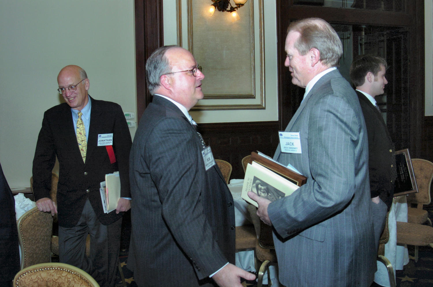 "[Jack Sweeney and Bob Carlquist], Photograph of Jack Sweeney (right) stopping to chat with Bob Carlquist during the 2005 Texas Daily News Association annual conference, held at the Driskell Hotel in Austin. Sweeney has been awarded the, ""2004 Mayborn Award for Community Leadership, presented to Jack Sweeney of the Houston Chronicle."" Jonathan Thompson is seen in the background.,"