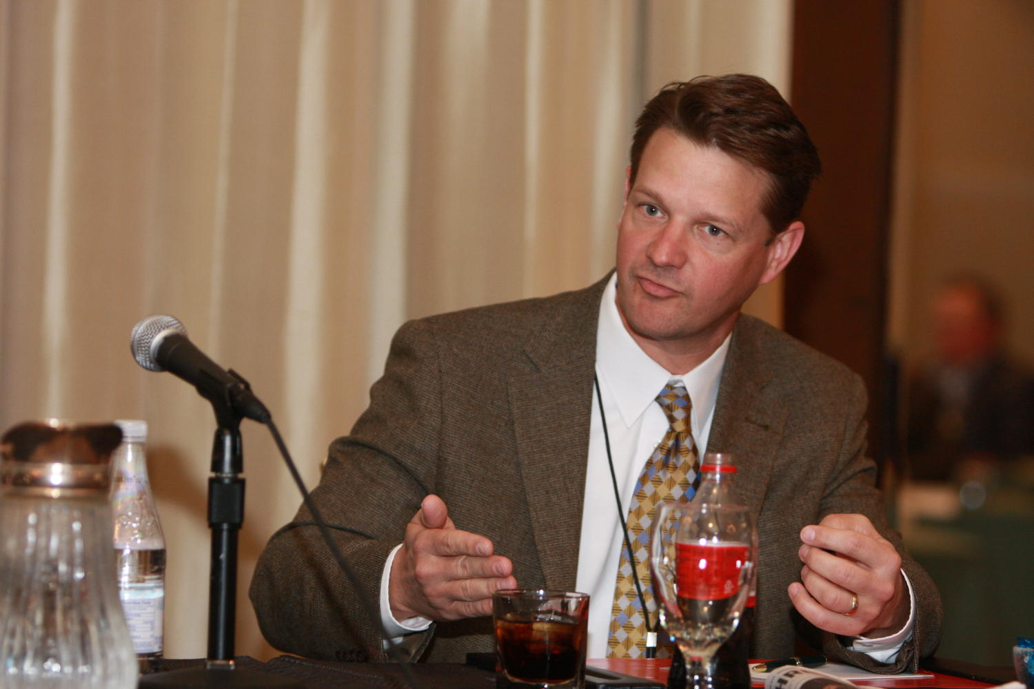 [Unidentified man seated at table during TDNA conference], Photograph of an unidentified man seated at a table with refreshments as he is attending the 2010 Texas Daily Newspaper Association annual meeting held in Houston, Texas.,