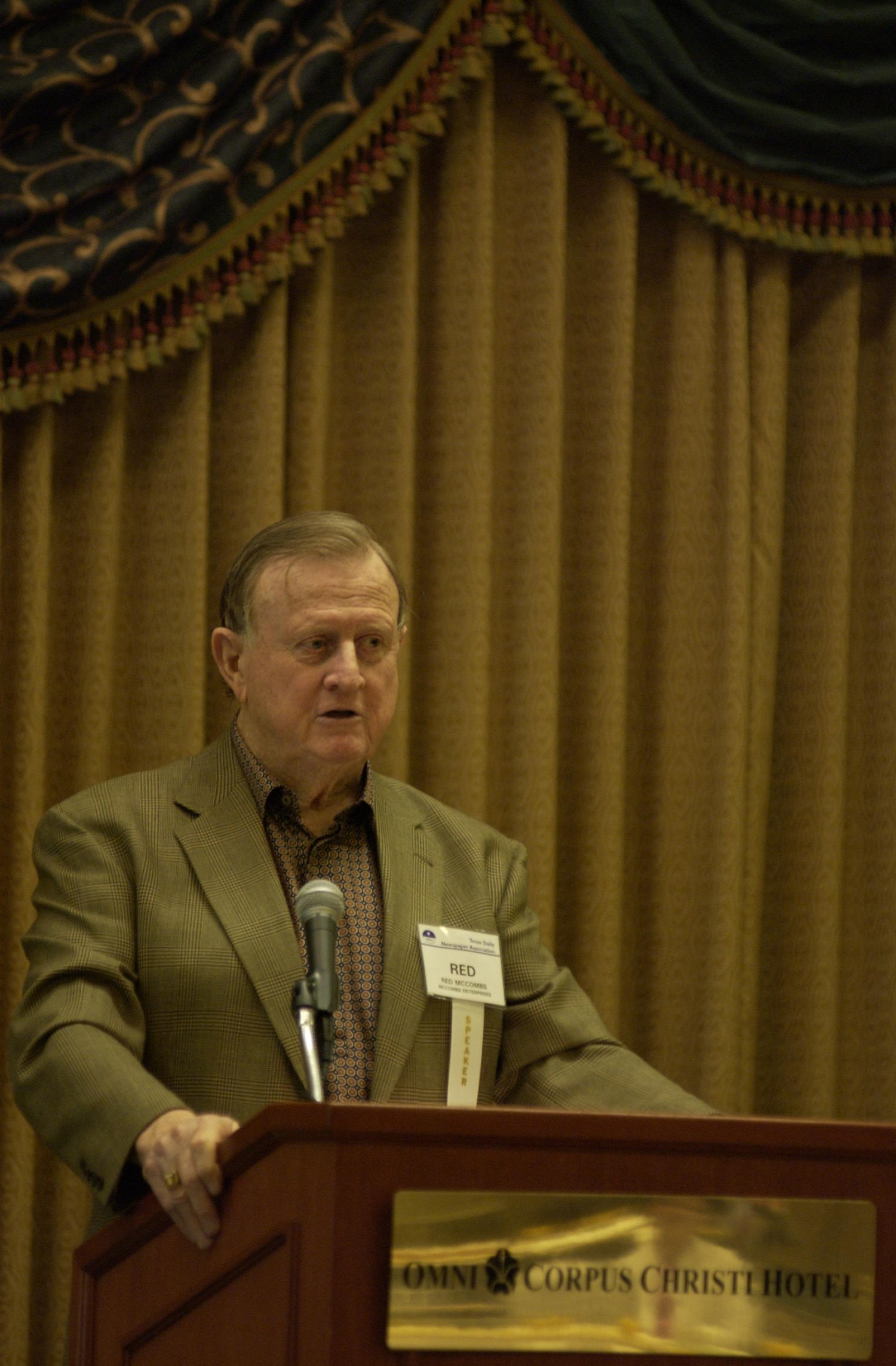 """[Billy Joe """"Red"""" McCombs guest speaking at TDNA conference, 2], Photograph of Billy Joe """"Red"""" McCombs of McCombs Enterprises, guest speaking at the 2004 Texas Daily News Association (TDNA) annual conference held in Corpus Christi. McCombs is seen standing at a podium and speaking into the microphone as he addresses the guests of the conference.,"""