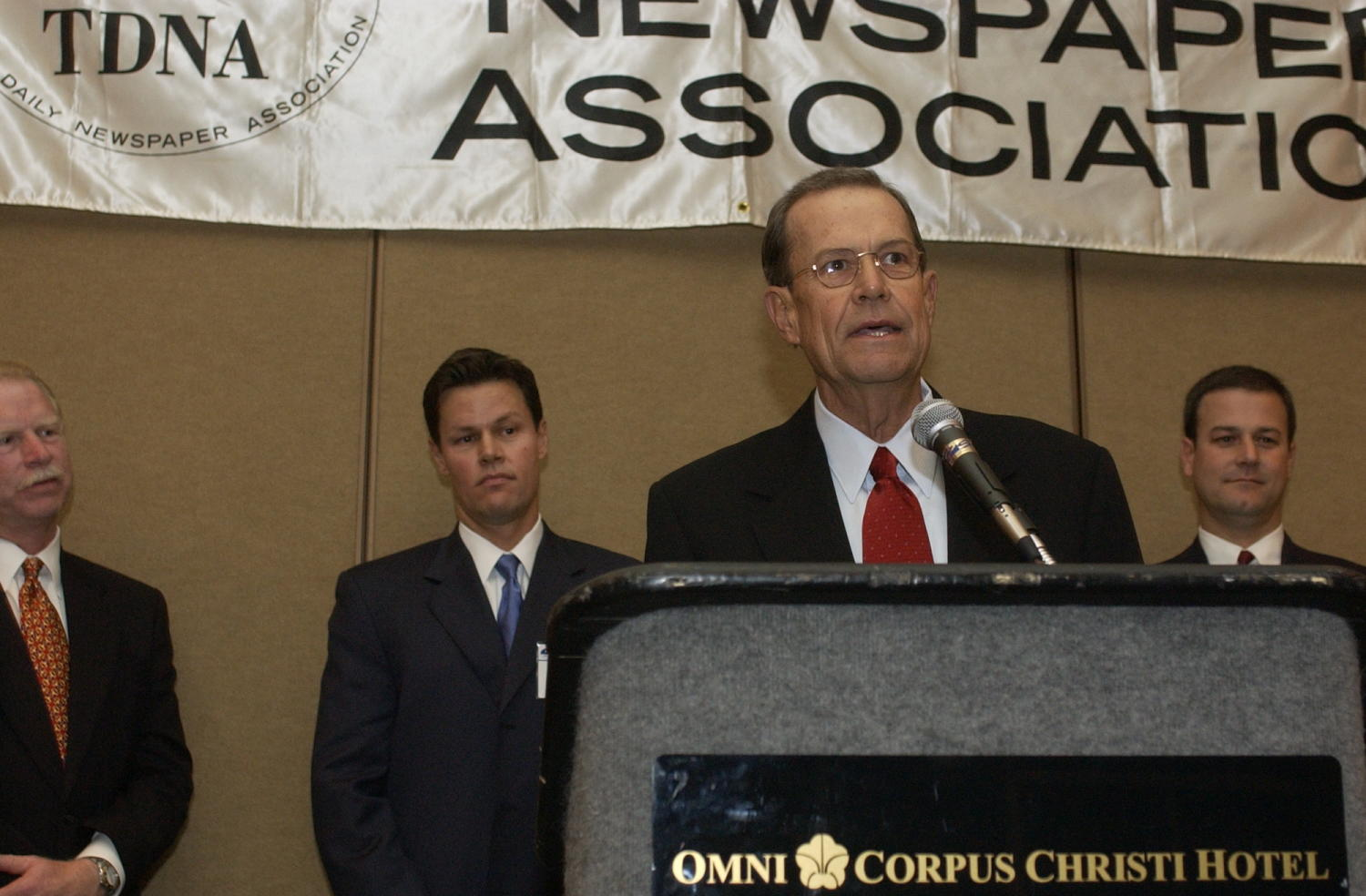 [Unidentified man speaking into microphone during TDNA conference], Photograph of an unidentified man speaking into the microphone during the 2004 Texas Daily News Association annual conference held in Corpus Christi. Donnis Baggett (left), and Fred Hartman (center) are seen standing against the wall and listening to the man address the other attendees in the audience during the conference.,