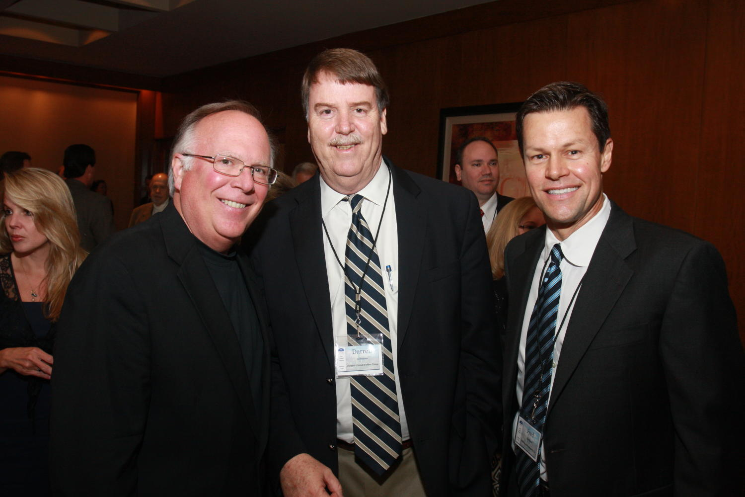 [Darrell Coleman and Fred K. Hartman], Photograph of three men, two identified as Darrell Coleman (center) and Fred K. Hartman (right) seen standing shoulder to shoulder, smiling, and posing for pictures during the 2010 Texas Daily Newspaper Association annual meeting held in Houston, Texas.,