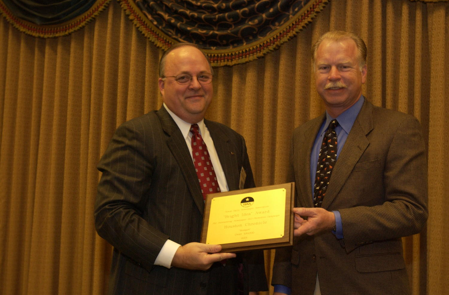 "[Man receiving award at TDNA Conference], Photograph of a Donnis Baggett (right) handing an engraved plaque to an unidentified man who is receiving the award from the 2004 Texas Daily News Association annual conference held in Corpus Christi. The plaque reads, ""TDNA. Texas Daily Newspaper Association. ""Bright Idea"" Award. For Outstanding Newspaper Self Promotion Campaign. Houston Chronicle. ""Hotspot"" Over 100,000. 2003"","