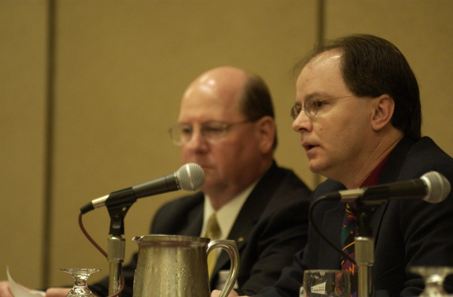 [Steve Jordan and Jack Light], Photograph of Steve Jordan (left) and Jack Light (right) in attendance at the 2004 Texas Daily News Association annual conference held in Corpus Christi. Jordan and Light are seen sitting behind a table and sitting in front of a microphones as they are guest speakers on a panel.,