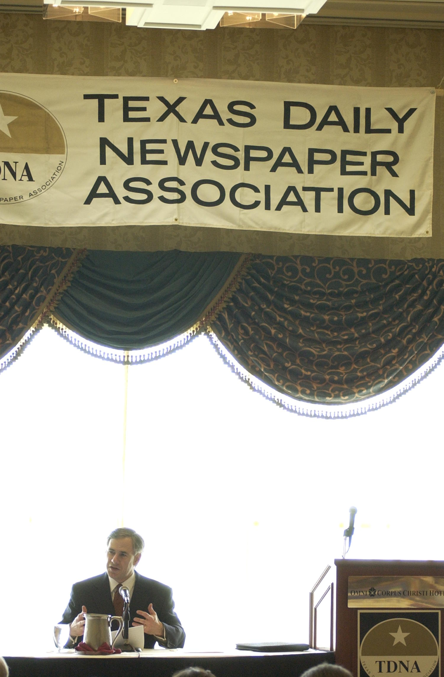 [Unidentified man attending the Texas Daily Newspaper Association conference], Photograph of an unidentified man seated in a chair and attending the 2004 Texas Daily News Association annual conference held in Corpus Christi. The man is seen speaking into the microphone placed in front of him and addressing the conference attendees. A large banner hangs above him that shows off the TDNA emblem.,
