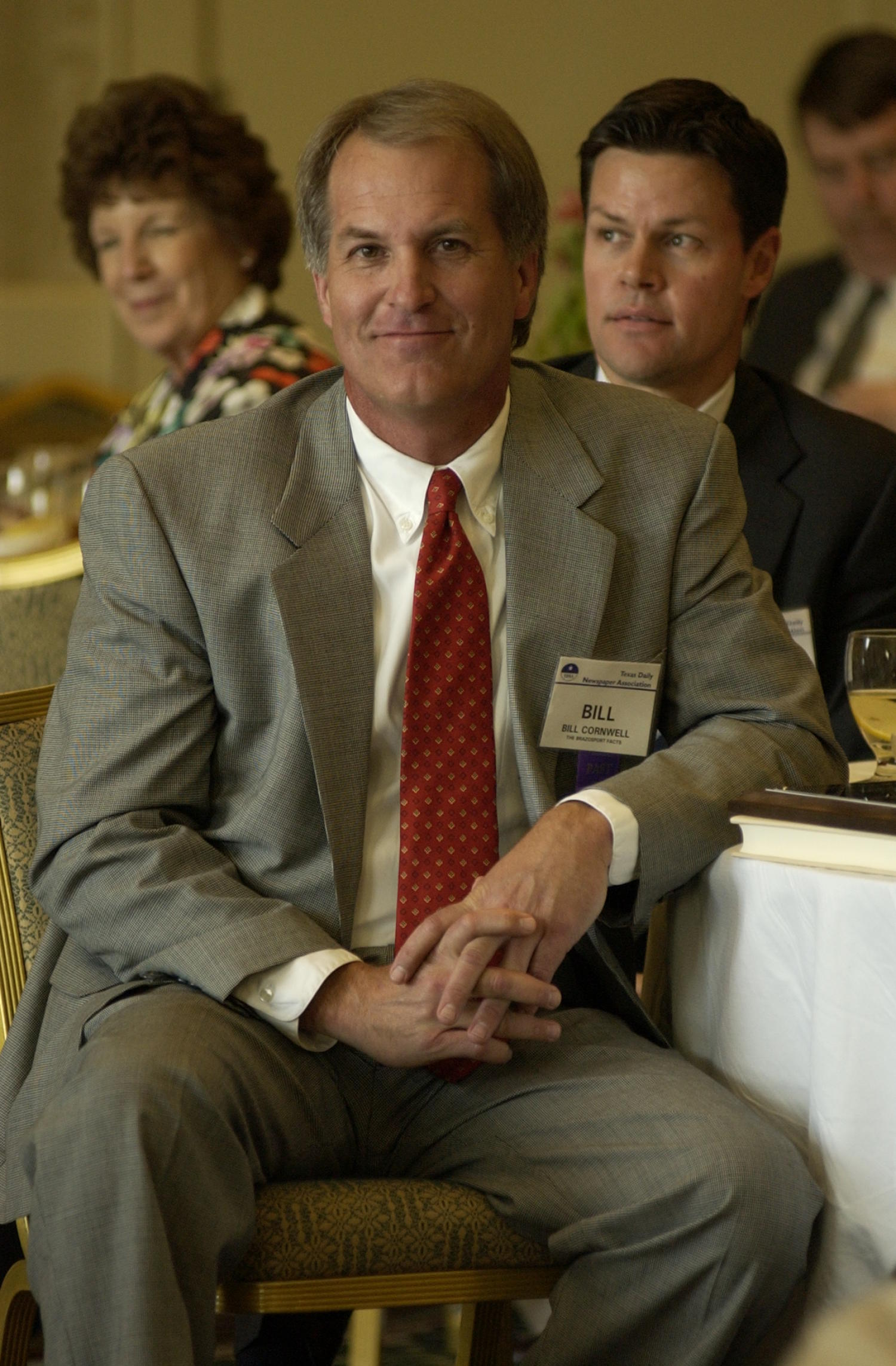 [Bill Cornwell attending a TDNA conference], Photograph of Bill Cornwell attending the 2004 Texas Daily News Association annual conference held in Corpus Christi. Cornwell is seen seated at his dinner table with his elbow resting on it as he looks at the photographer and smiles.,