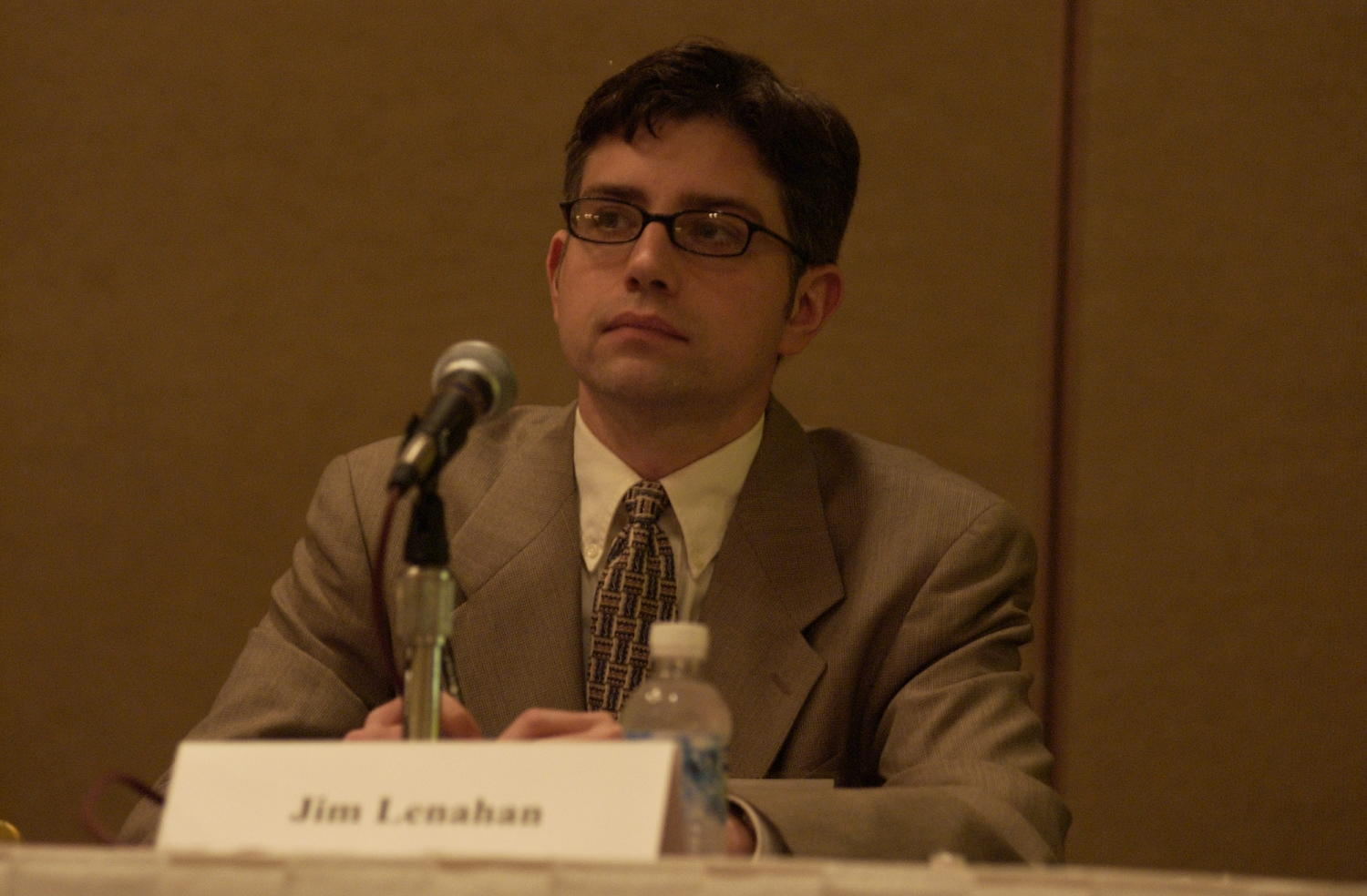 [Jim Lenahan attending TDNA conference], Photograph of Jim Lenahan, a guest speaker attending the 2004 Texas Daily News Association annual conference held in Corpus Christi. Lenahan is seen seated behind a table and in front of a microphone as he is on a panel of other guest speakers at the conference.,