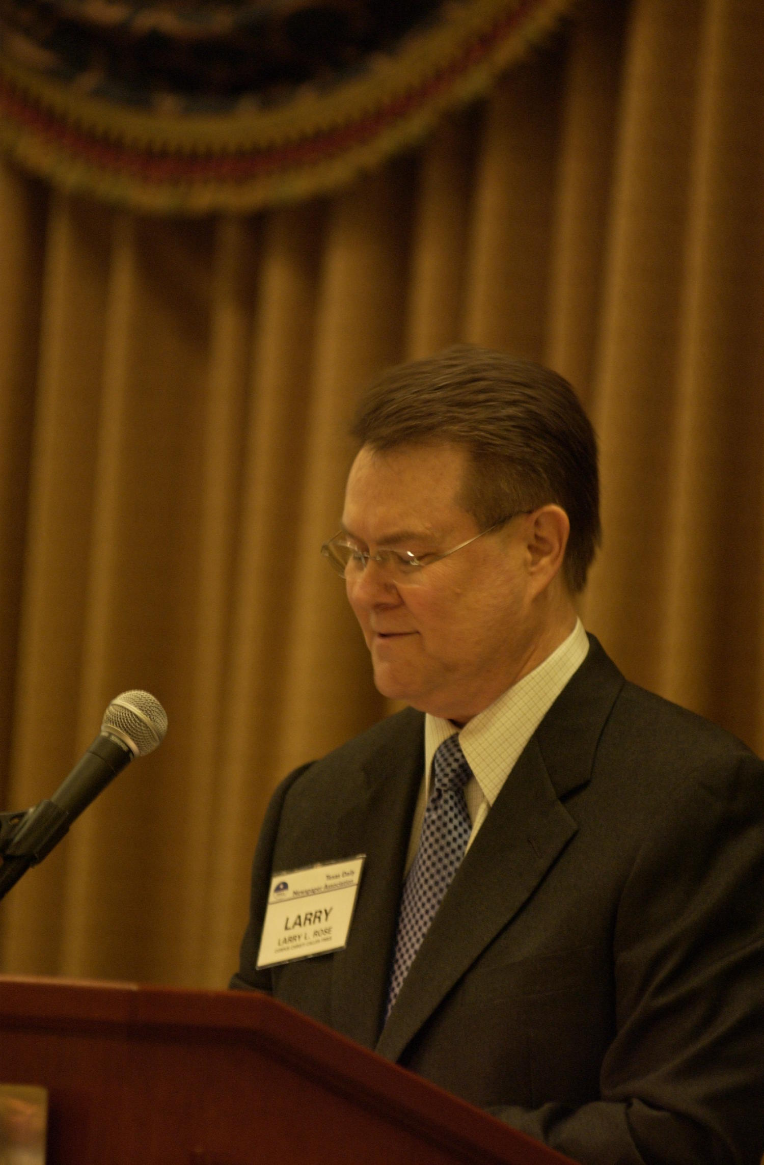 [Larry L. Rose guest speaking at TDNA conference], Photograph of Larry L. Rose, guest speaking at the 2004 Texas Daily News Association (TDNA) annual conference held in Corpus Christi. Rose is seen standing at the podium and looking down at his notes, the microphone a foot away from him.,