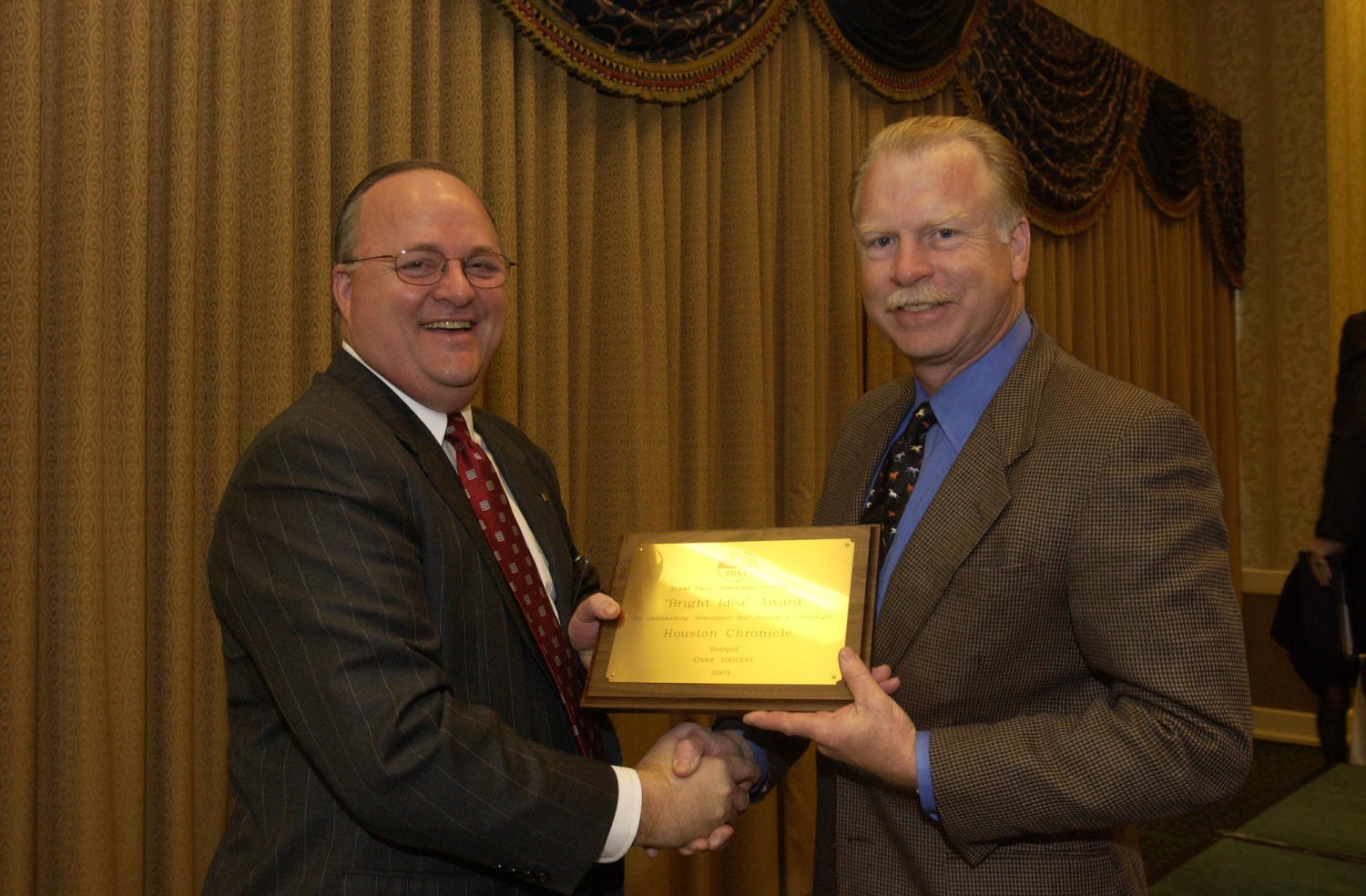 """[Man receiving award at TDNA Conference, 2], Photograph of a Donnis Baggett (right) handing an engraved plaque to an unidentified man who is receiving the award from the 2004 Texas Daily News Association annual conference held in Corpus Christi. The plaque reads, """"TDNA. Texas Daily Newspaper Association. """"Bright Idea"""" Award. For Outstanding Newspaper Self Promotion Campaign. Houston Chronicle. """"Hotspot"""" Over 100,000. 2003"""","""