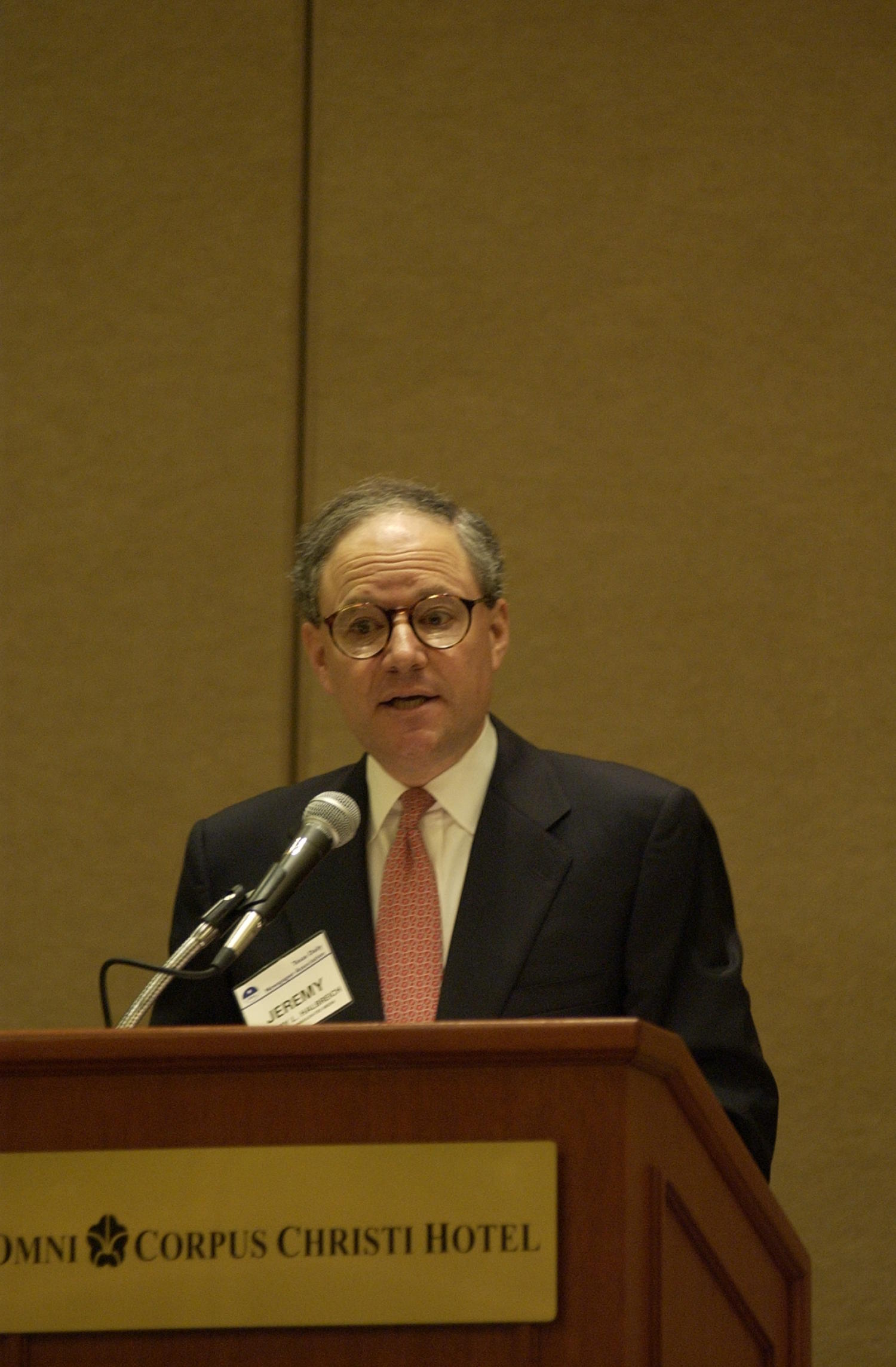 [Guest speaker Jeremy L. Halbreich at TDNA conference], Photograph of Jeremy L. Halbreich, a guest speaker attending the 2004 Texas Daily News Association annual conference held in Corpus Christi. Halbreich is standing at a podium in the conference hall and talking into the microphone addressing the attendees.,