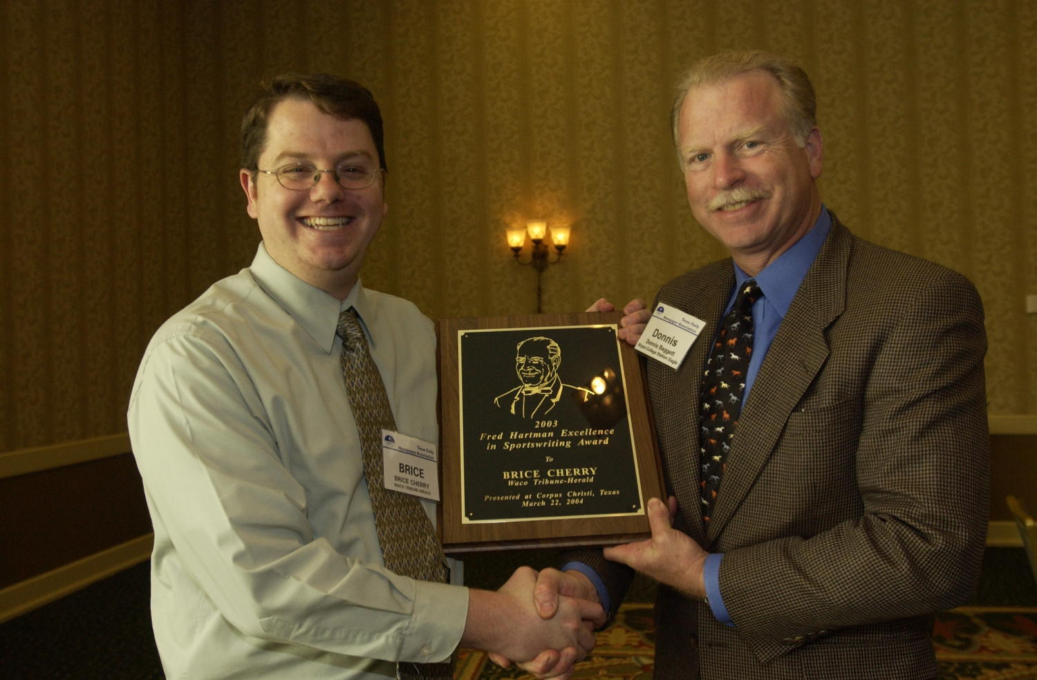 """[Donnis Bagget handing out plaque award to Brice Cherry], Photograph of Donnis Bagget (right) handing an engraved plaque to Brice Cherry, who is receiving the award from the 2004 Texas Daily News Association annual conference held in Corpus Christi. The plaque reads, """"2003 Fred Hartman Excellence in Sportswriting Award to Brice Cherry. Waco Tribune-Herald. Presented at Crrpus Christi, Texas March 22, 2004."""","""